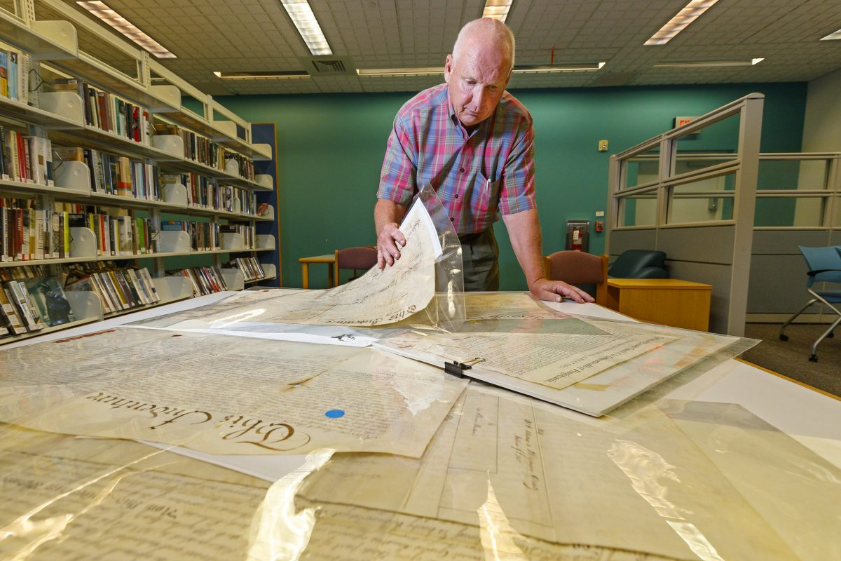 Jim Reis looks through his collection of historical deeds.