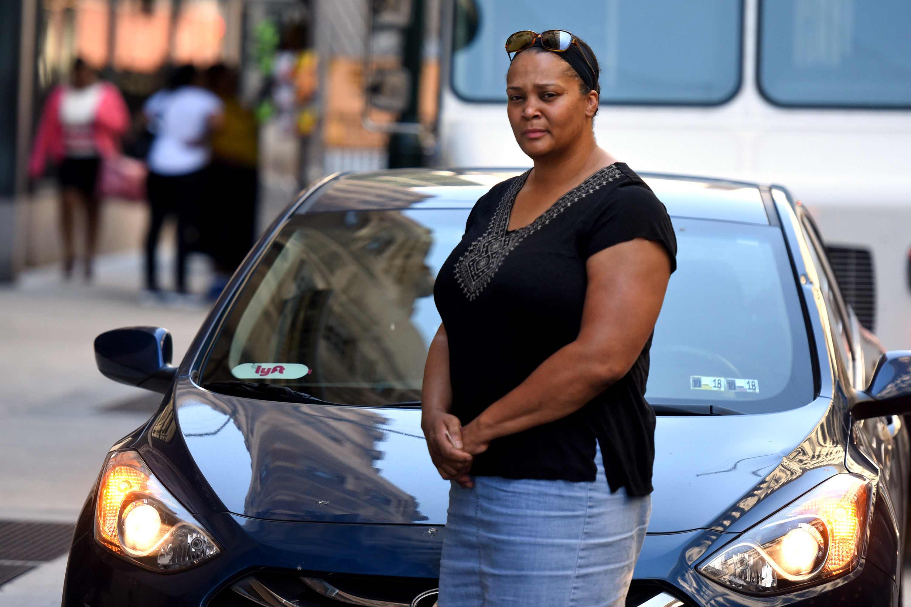 Lyft driver Kenita Jalivay poses outside her vehicle July 9, 2018. The previous night she was trapped in the middle of a shooting scene, and Lyft gave her $5 reimbursement for her trouble and her trauma, having to cancel her last ride. TOM GRALISH / Staff Photographer