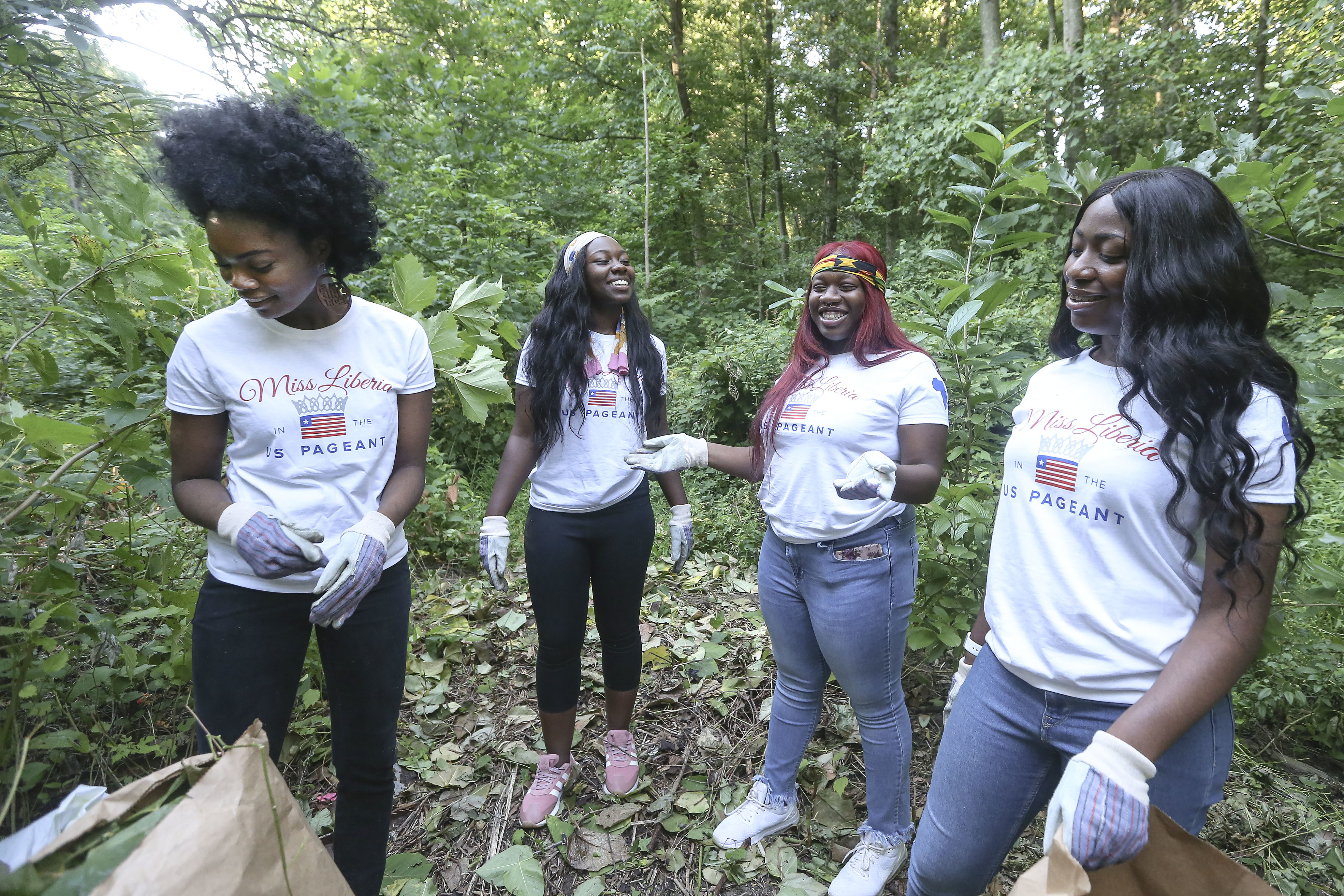 Miss Liberia Pageant contestants (l-r) Naomi Glay, Aba Aggrey, Alberta Richards and Rudmita Mark working on a service project with Royal Gardens cleaning up Morris Park in Overbrook, Wednesday, July 18, 2018.
