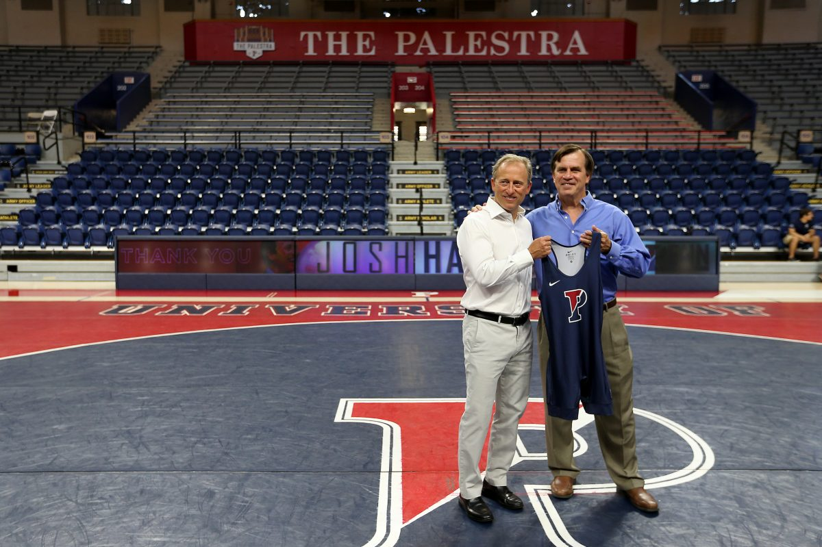 Sixers owner Josh Harris, left, with Roger Reina,  Penn wrestling coach, after he announced a $1 million gift to Penn wrestling.