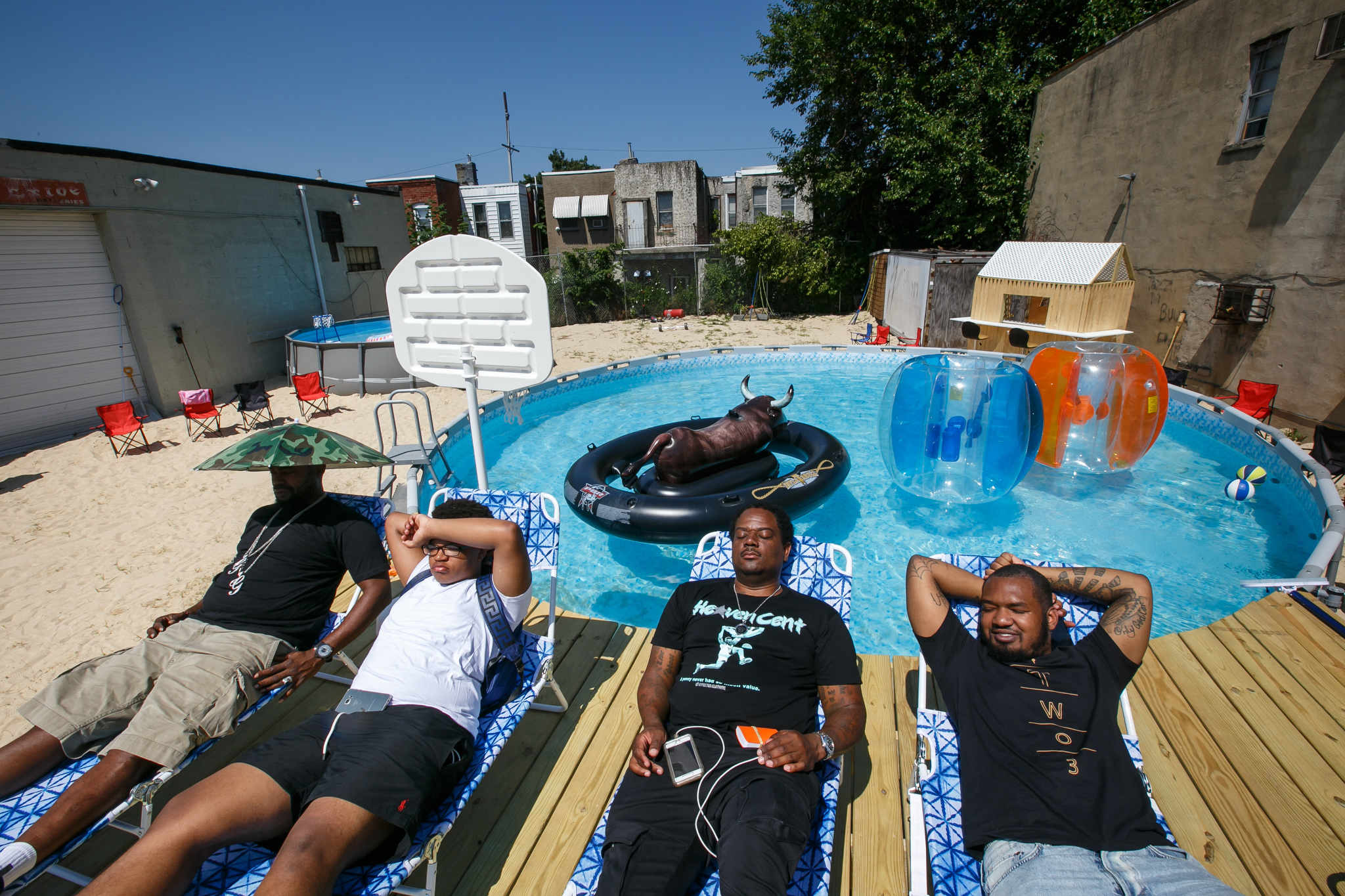 Relaxing poolside, the owners and promoter await an upcoming pool party on a vacant North Philadelphia lot Wednesday, July 11, 2018. They converted it into a miniature beach with sand, above ground pools, a wooden deck and beach furniture.