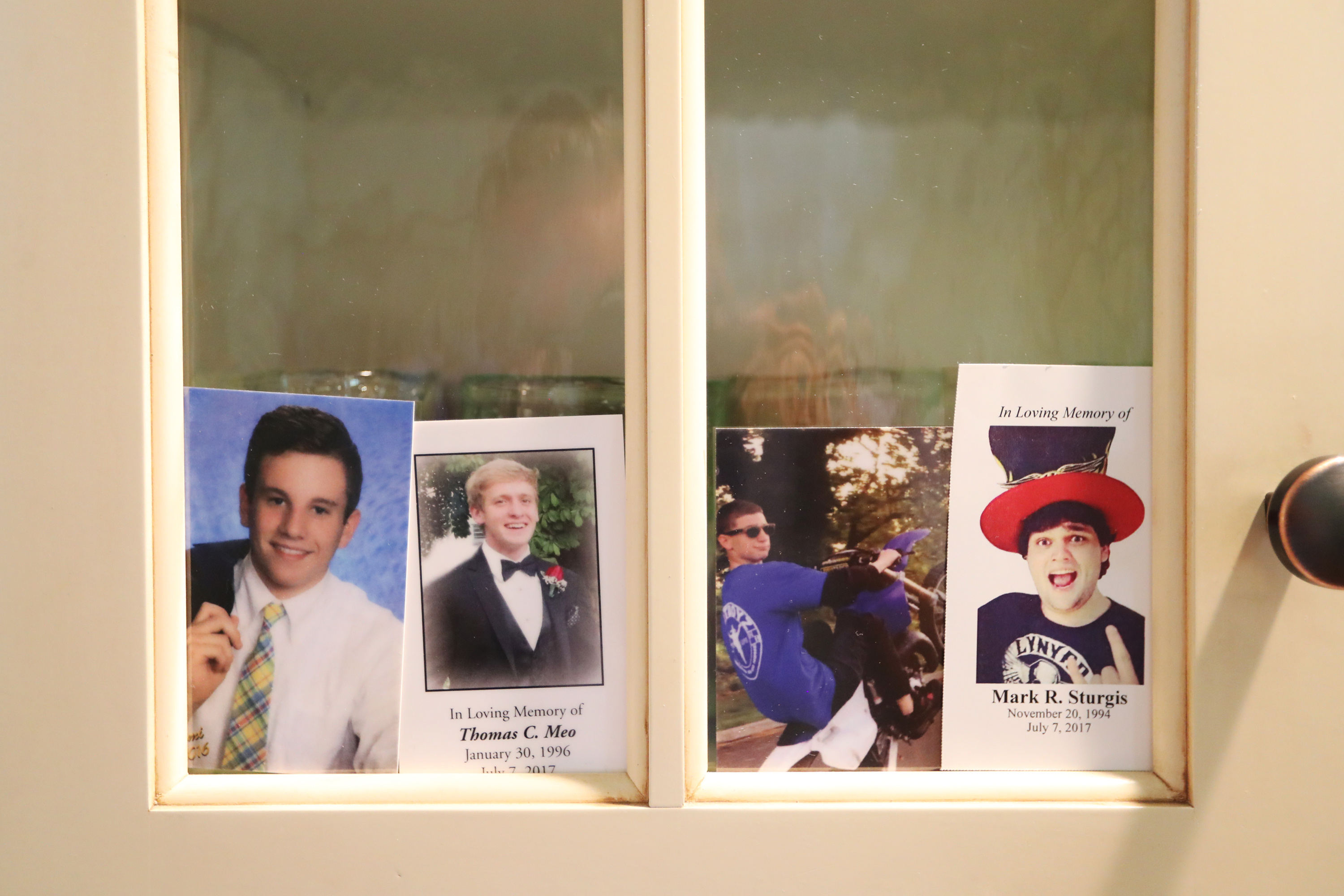(L-R) Four photos of Jimi Patrick, Tom Meo, Dean Finocchiaro, and Mark Sturgis are placed in a kitchen cabinet window in the home of the Patricks, nearing the anniversary of the July 2017 murders of the four young men in Bucks County. DAVID SWANSON / Staff Photographer