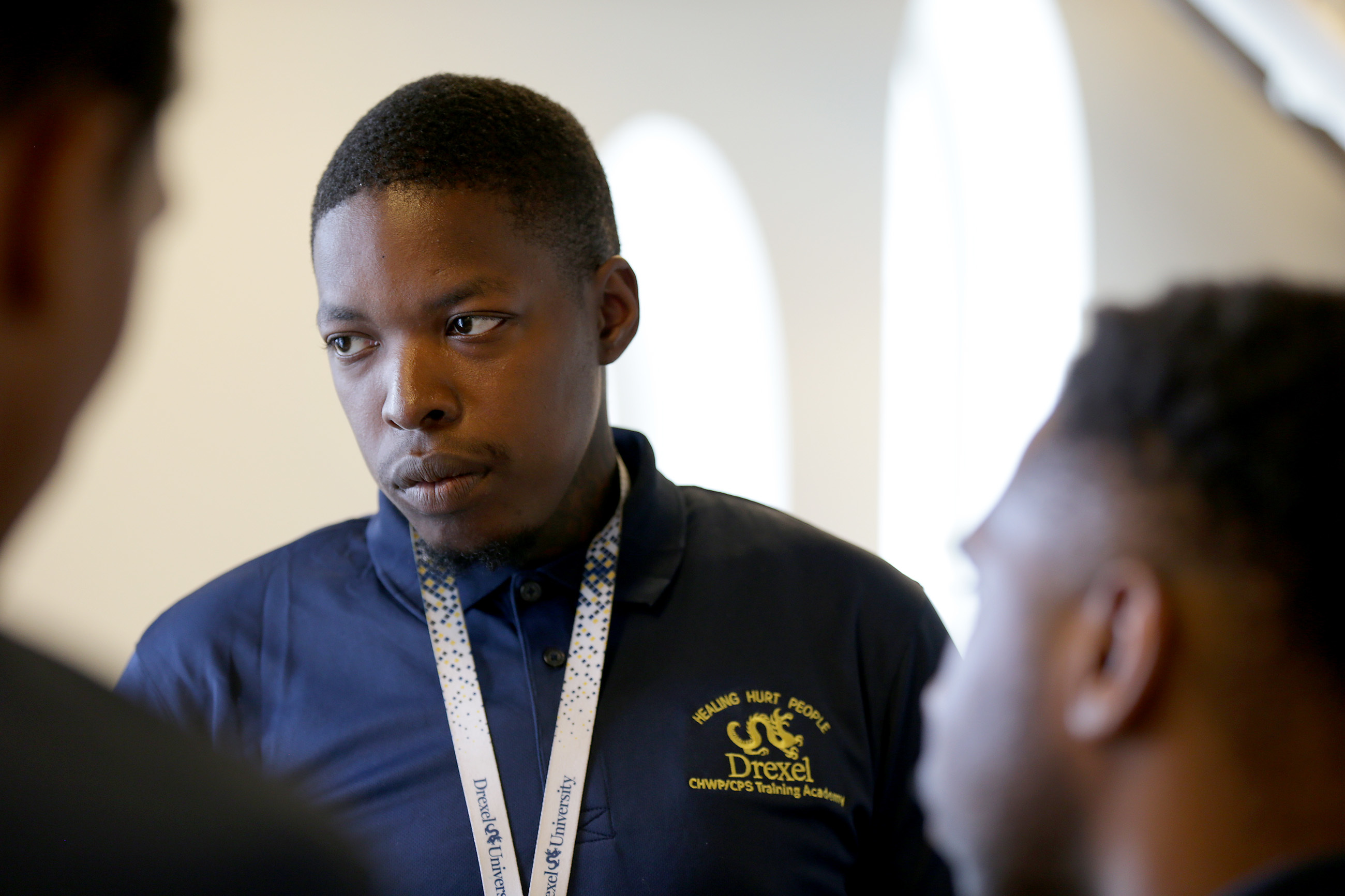 Anthony Miles, center, talks with his classmates before the Drexel University CHWP/CPS Training Academy graduation in Philadelphia, PA on July 12, 2018.