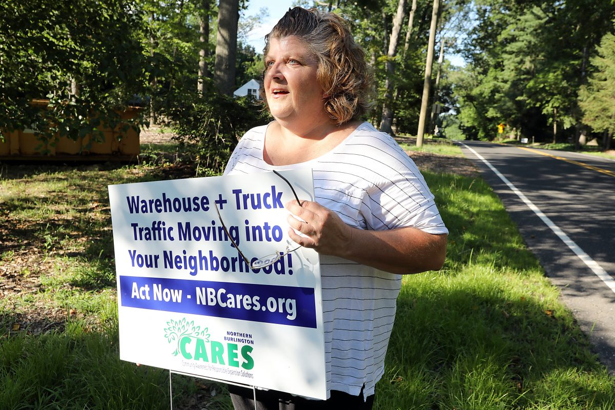 Beth Camp, who helped organize NBCares, shows a sign she planted in front of her family home to work against an onslaught of tractor-trailers that could have come down her street from a giant warehouse project in Mansfield Township, N.J.