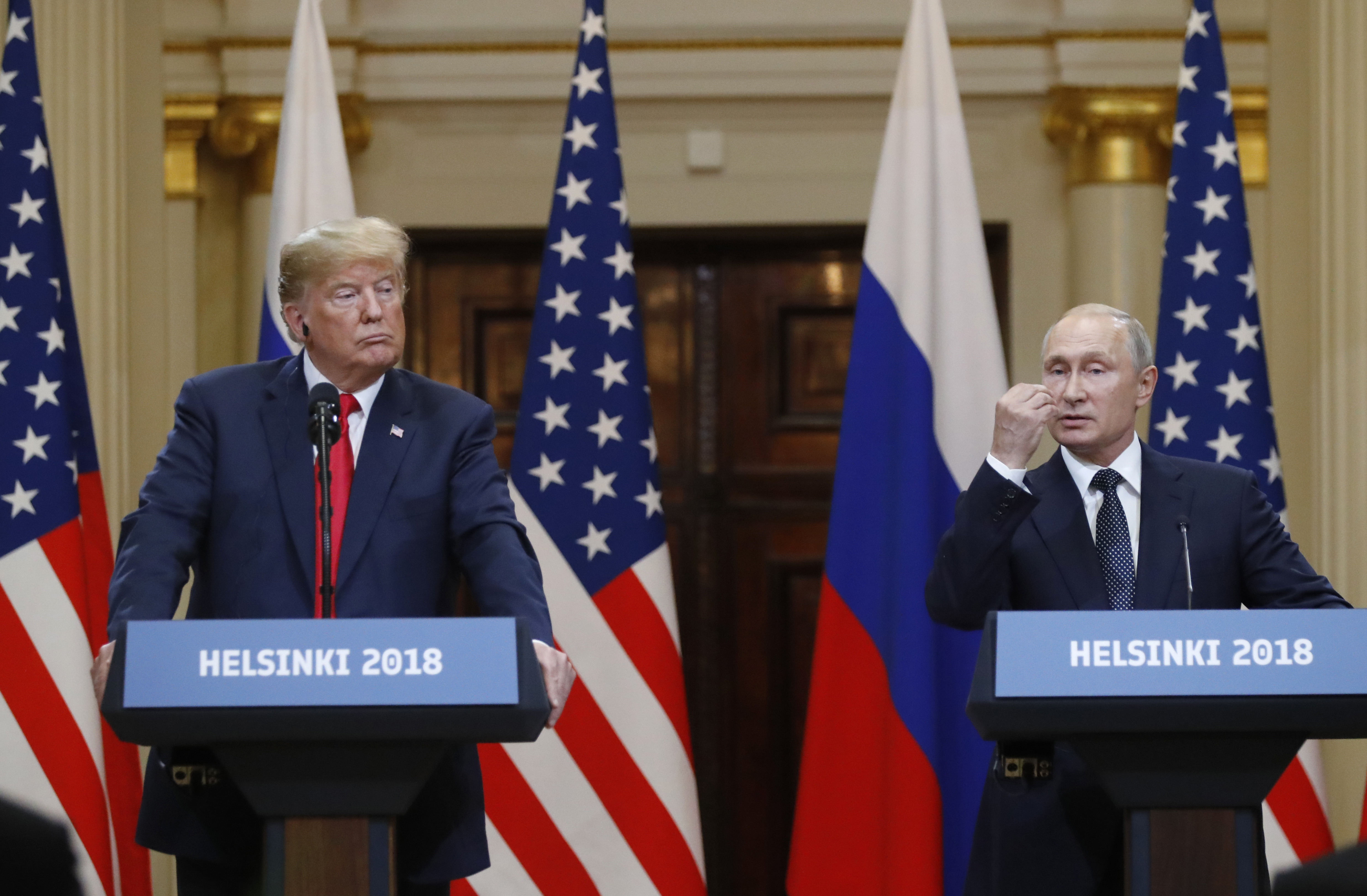 U.S. President Donald Trump, left, listens to Russian President Vladimir Putin during a press conference after their meeting at the Presidential Palace in Helsinki, Finland, Monday, July 16, 2018.