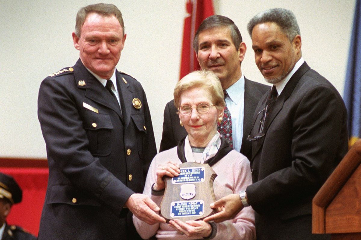 Carmella Rizzo is seen at the graduation ceremony of the Philadelphia Police College Class 331 and the retiring of the badge of her husband, former Police Commissioner and Mayor Frank Rizzo. She is flanked by John F. Timoney, left, and John Street. Directly behind Mrs. Rizzo is her son, Francis S. Rizzo.