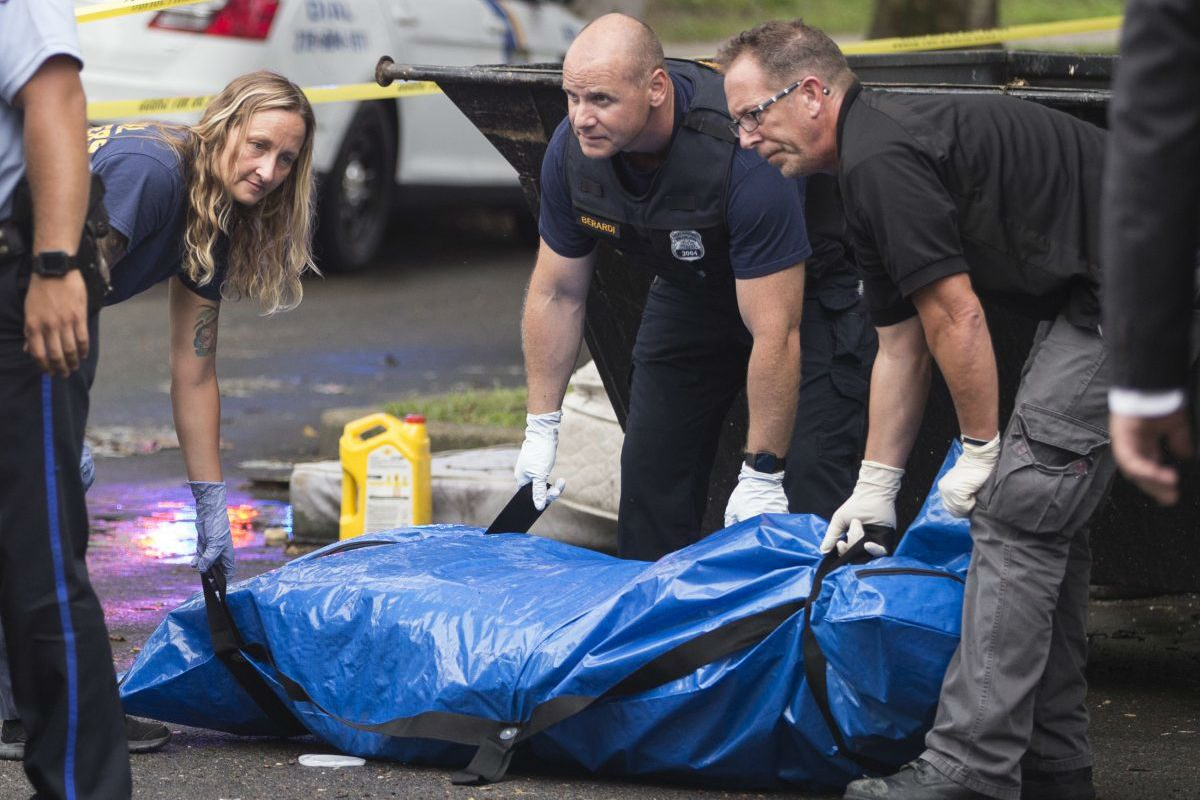 The body of a female was found inside a large suitcase in a dumpster at the Bartram Gardens Housing Project on July 17, 2018. Housing workers called the police after noticing the stench. The suitcase and body are prepred to be loaded into a police vehicle after being place in a blue bag.