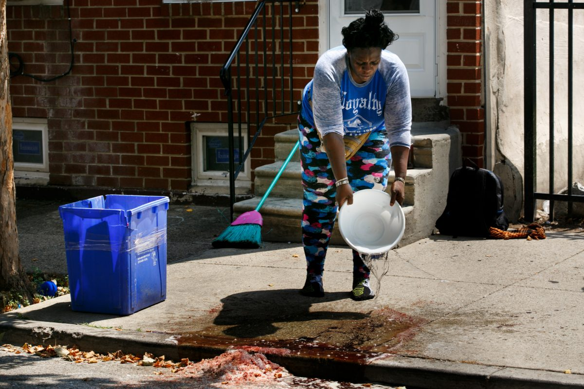 """A woman who prefers to be identified by her nickname, """"Tank,"""" cleans blood off the sidewalk on the 2100 block of North Fourth Street, Tuesday, July 17, 2018."""