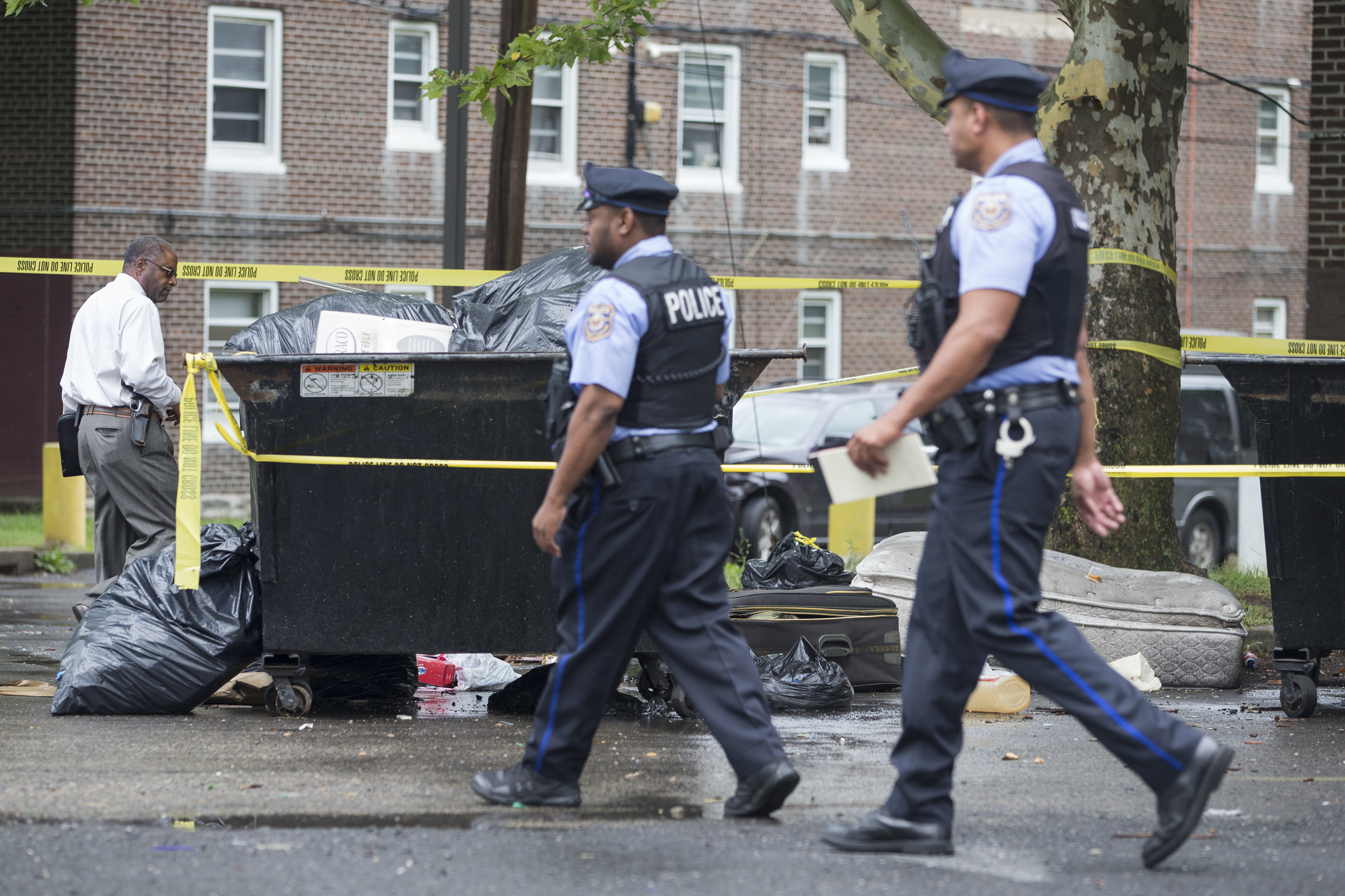 A decomposing body was found inside the suitcase seen here between two Philadelphia police officers on Tuesday, July 17, 2018, at the Bartram Gardens housing project in Southwest Philadelphia.