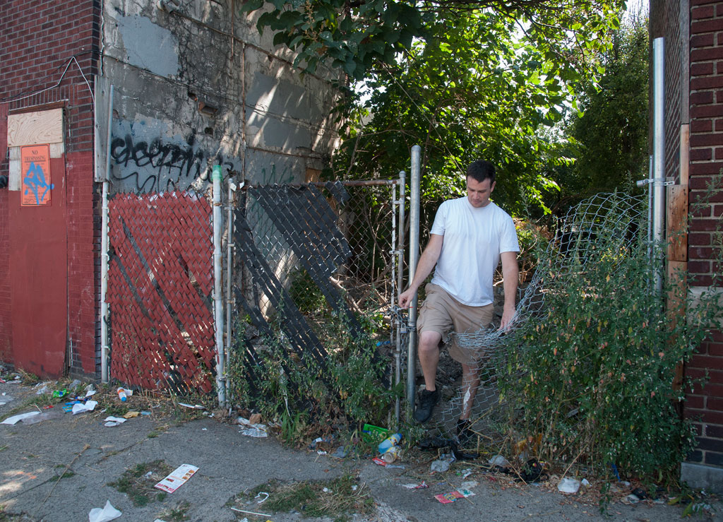 Jamie Moffett, a community activist in the Harrowgate neighborhood, climbs through a broken fence at 3366 Rand St -- a half-a-block from the 3300 block of Argyle St. -- where people who buy drugs on Argyle St. go to shoot up. The 3300 block of Argyle St. is a microcosm of a poor city block in one of the city's poorest sections – a look at how hard it is to bring a block back after decades of decline. ( CLEM MURRAY / Staff Photographer )