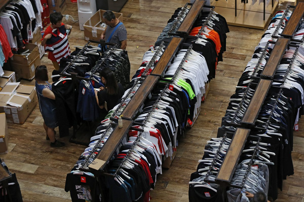 People try garments at a retail and wholesale clothing mall in Beijing.