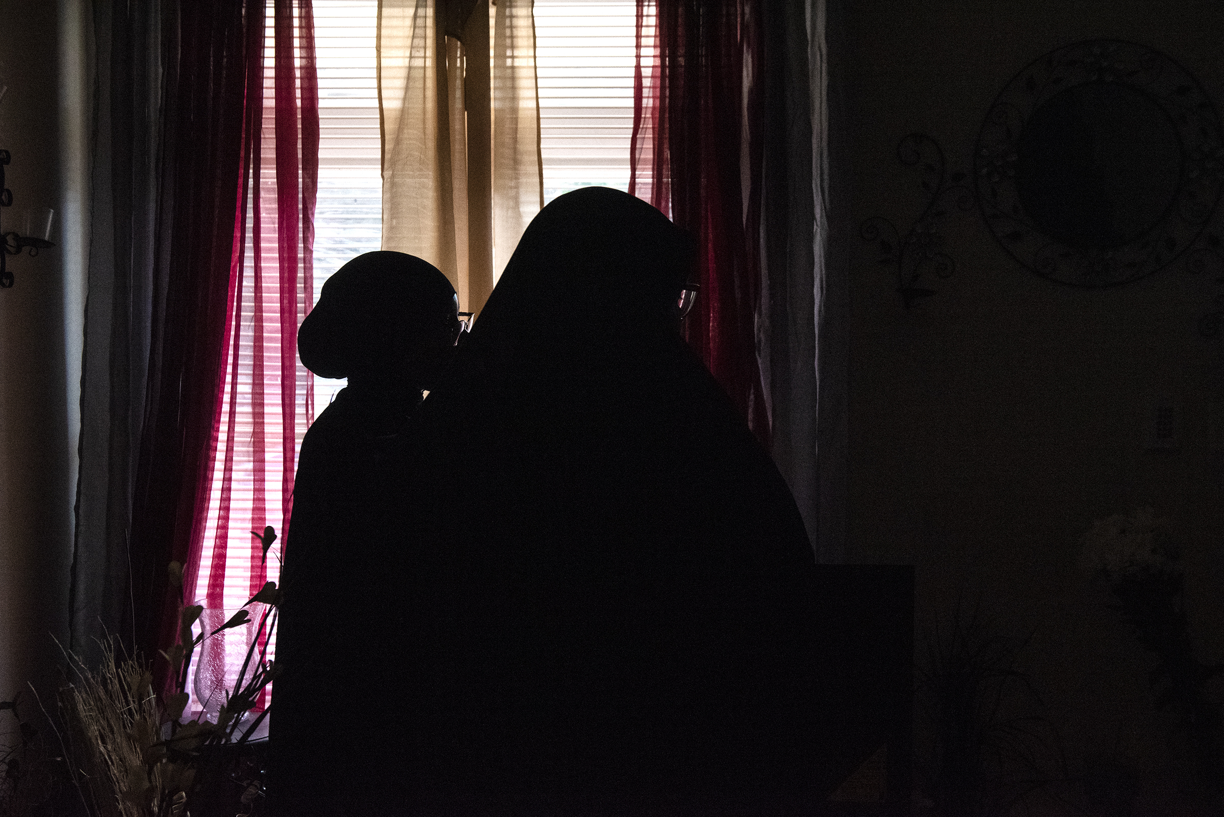 The silhouette of Aleah Johnson, right, and her daughter Sanaa Sawyer, 14, inside their home in West Philadelphia on Friday, July 20, 2018. Johnson was banned from Sesame Place on Saturday after she was accused of stealing from a park gift shop. She thinks she was profiled because of her race and religion.