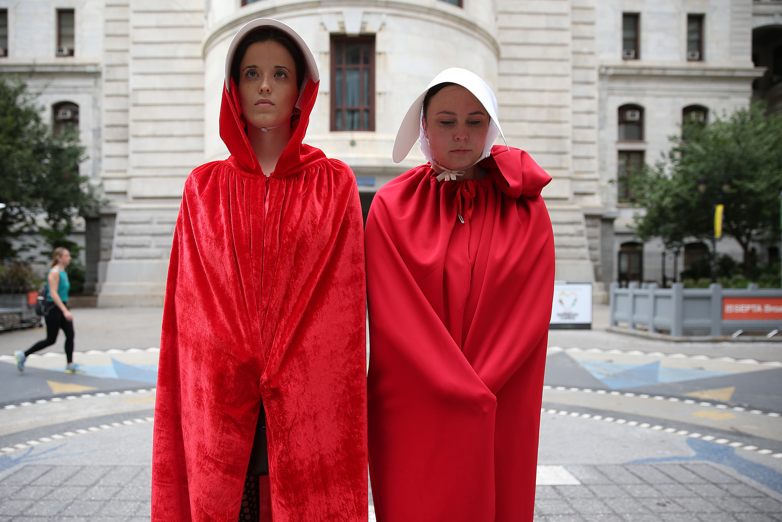 Protesters Mary Tierney, left, and Liz McHale, right, wait at City Hall dressed in costumes from the Handmaid's Tale as Vice President Mike Pence makes a stop at the Union League in Philadelphia, PA on July 23, 2018.