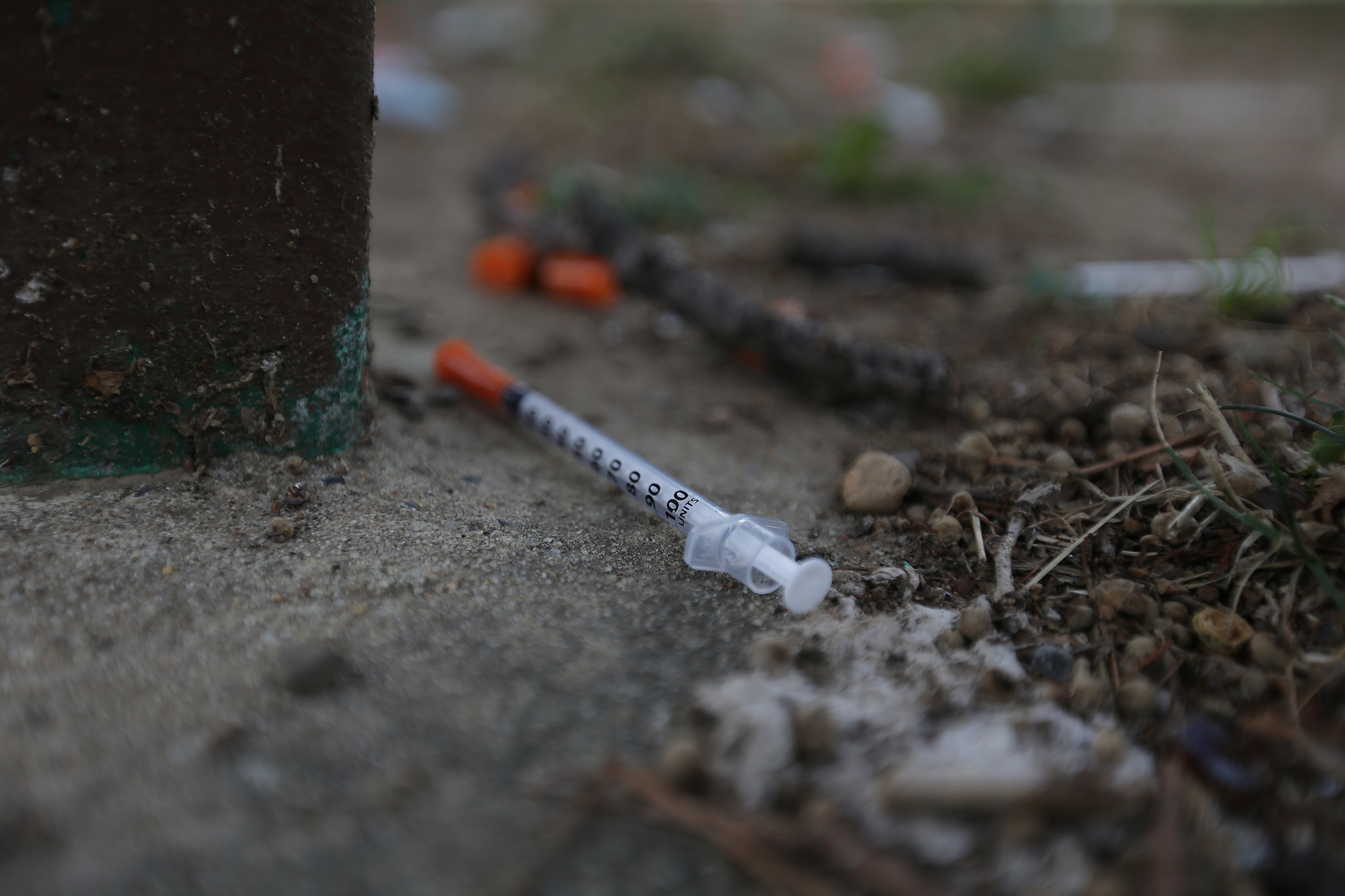 A needle sits next to a bench on the lawn around McPherson Square Library.