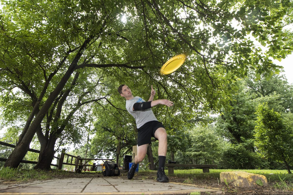 Alex Caldwell, throws a flying disc at the Sedgley Woods' 27-hole disc golf course in East Fairmount Park.