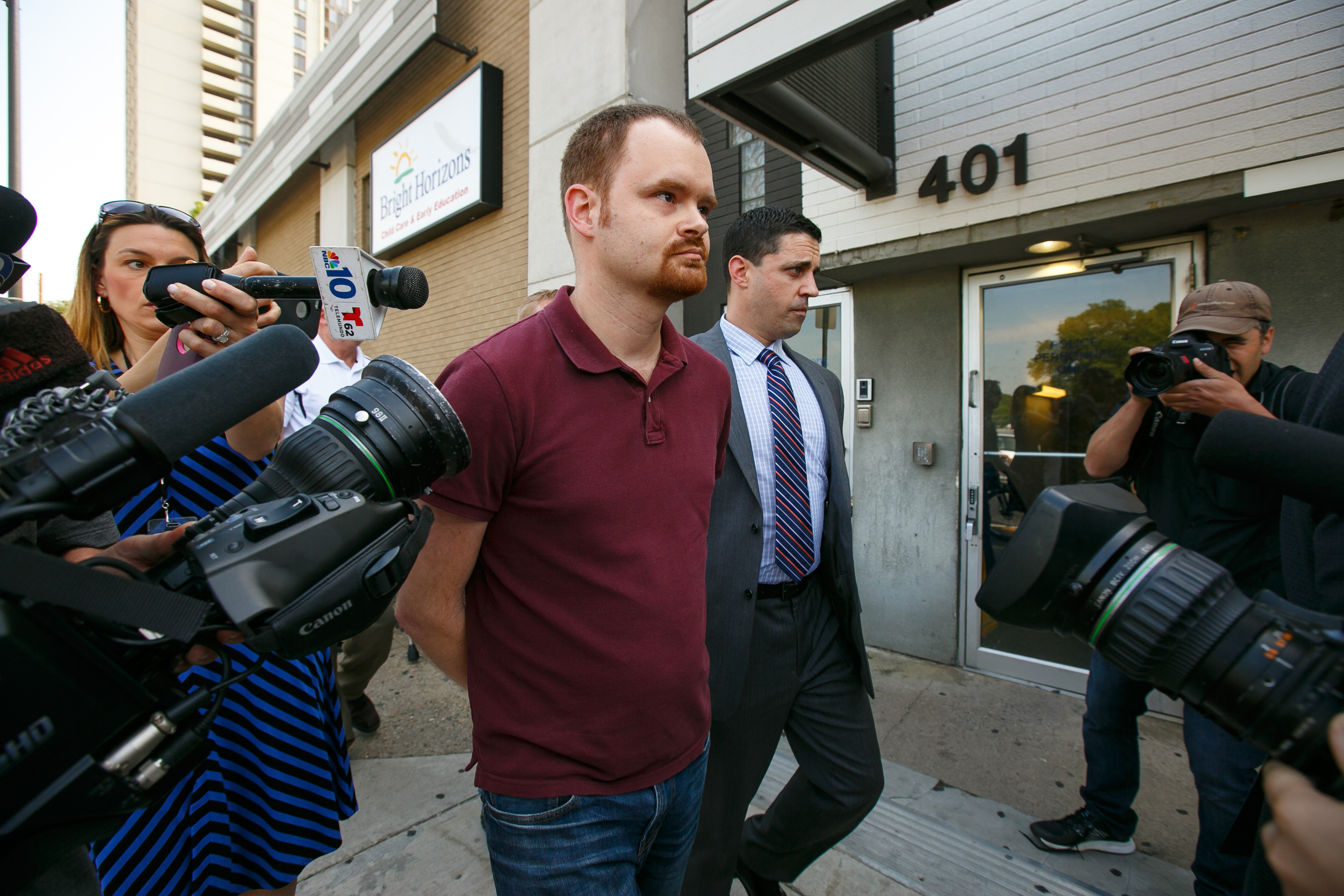 Brandon Bostian, center, the Amtrak engineer, turns himself in to the 9th district police station in Philadelphia.