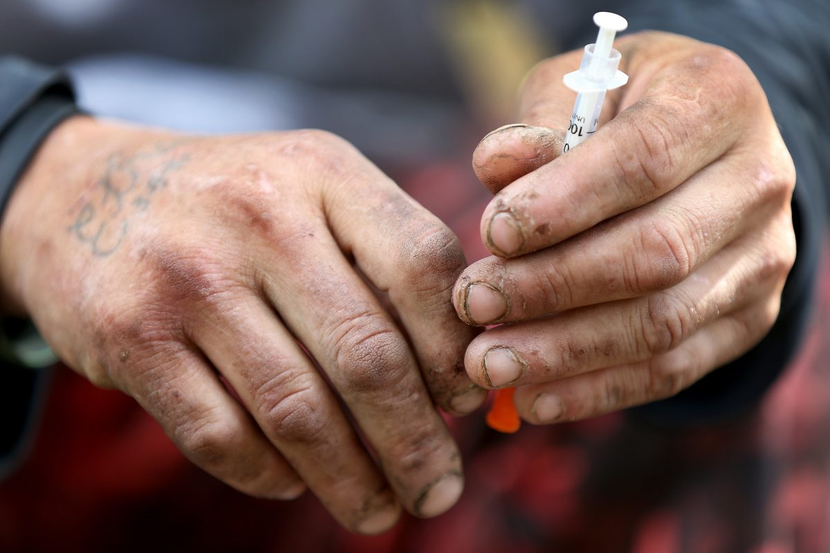 A heroin user holds a needle after injecting himself along the railroad track in Kensington in Philadelphia, PA on October 25, 2017. DAVID MAIALETTI / Staff Photographer