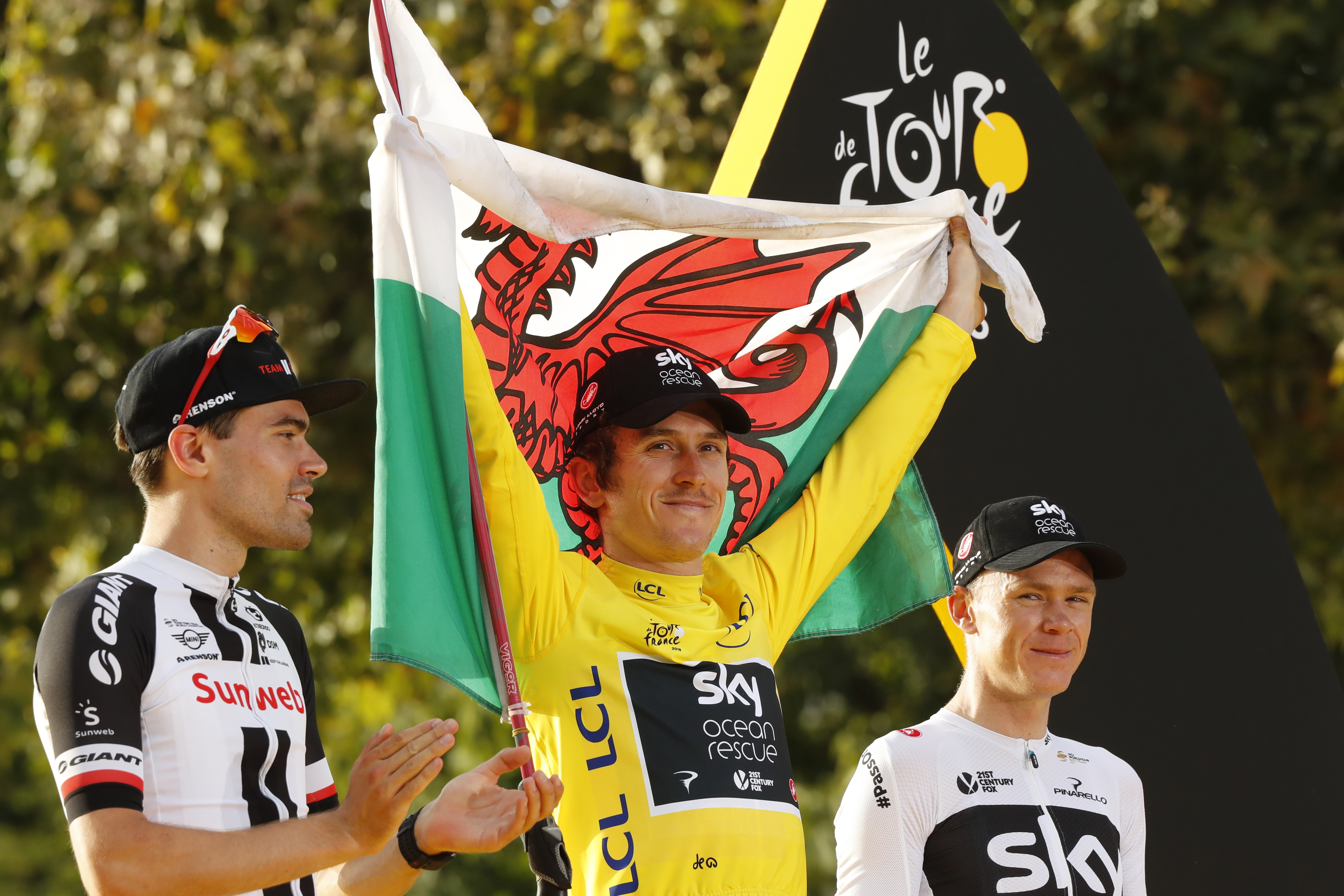 Britain´s Geraint Thomas (center) celebrates his Tour de France victory while wearing the overall leader´s yellow jersey and waving the Welsh flag on Sunday. The Netherlands´Tom Dumoulin (left) finished second; Britain´s Chris Froome (right) finished third.