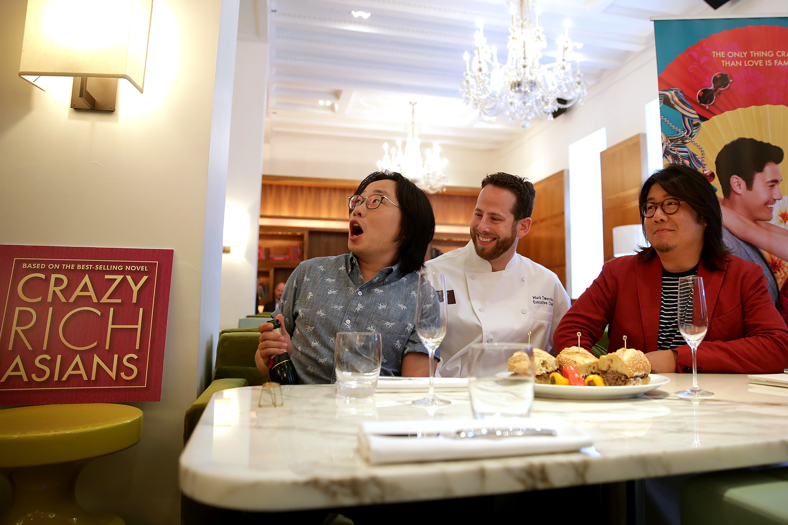 "Actor Jimmy O. Yang, left, reacts to popping open a bottle of champagne as Chef Mark Twersky, center, and writer Kevin Kwan, right, watch during a promotional event for the movie ""Crazy Rich Asians"" at Barclay Prime in Philadelphia, PA on July 31, 2018."