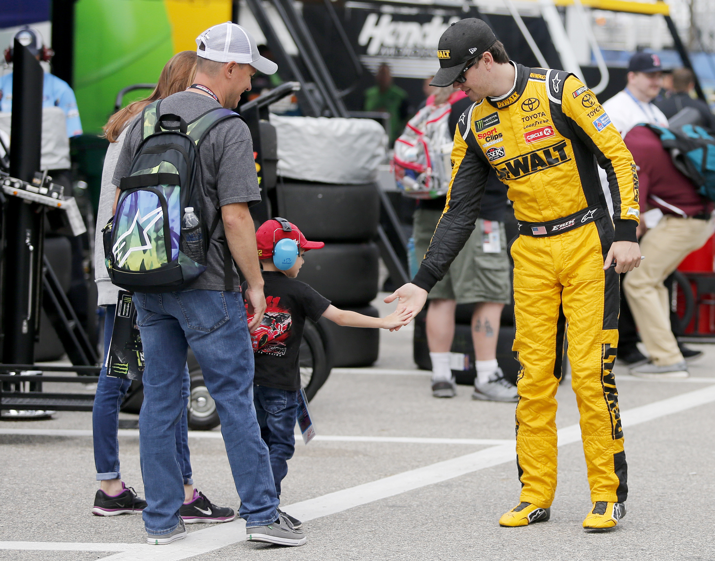 Erik Jones gets a high five from Jake Manalio, 4, of Middletown, N.Y., as he walks to his car at the start of practice for the NASCAR Cup Series auto race Saturday, July 21, 2018, at New Hampshire Motor Speedway in Loudon, N.H. (AP Photo/Mary Schwalm)