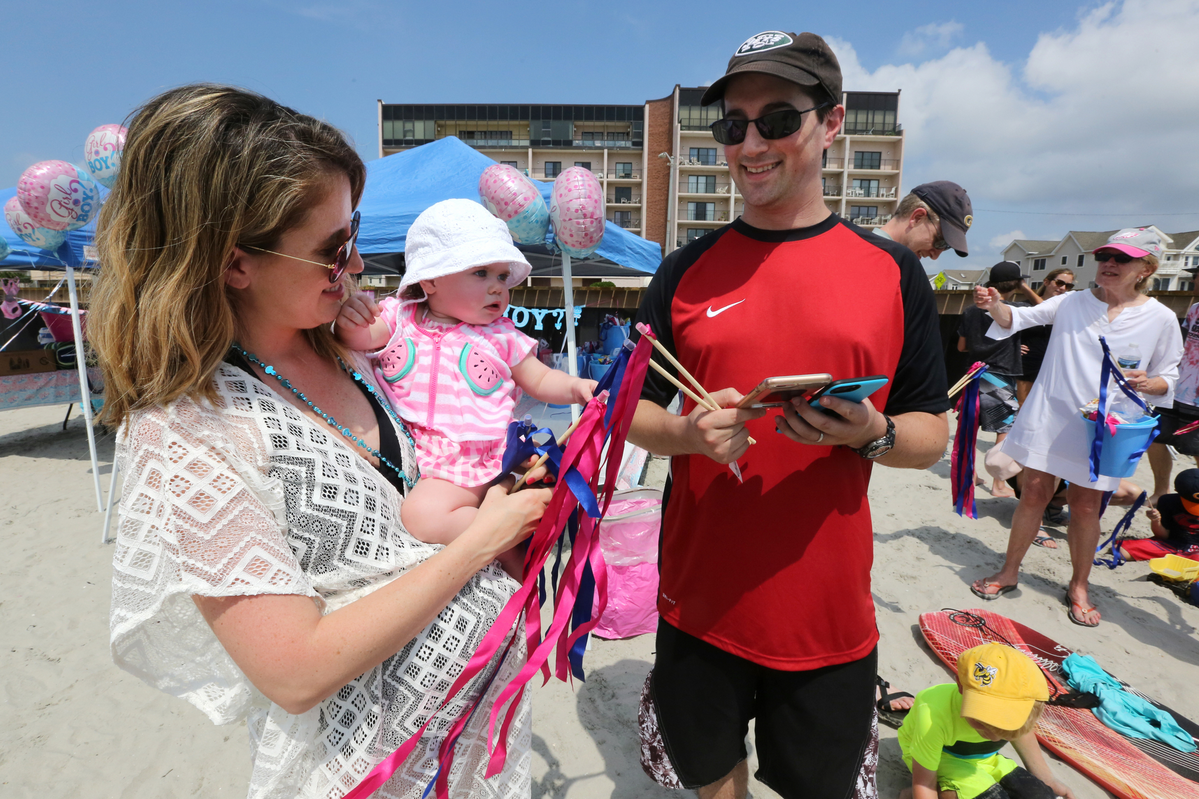 Lauren and Michael Norden, of Robbinsville, with their daughter, Emily, Saturday, July 28, 2018, on the beach off 5th Street, in North Wildwood. Later, a banner plane announced the gender of their expectant baby. Vernon Ogrodnek / For the Inquirer