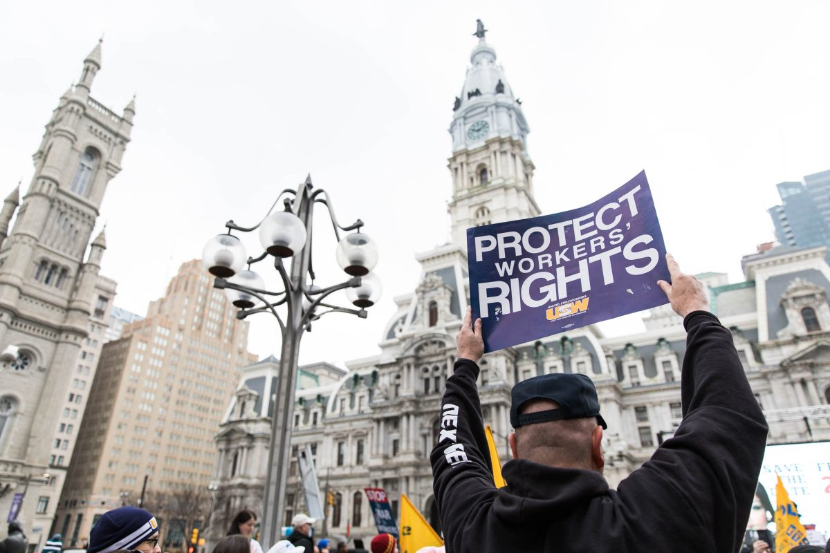 "A attendee of Working People's Day of Action rally in February  in Thomas Paine Plaza holds up a sign that reads ""Protect Workers' Rights."""