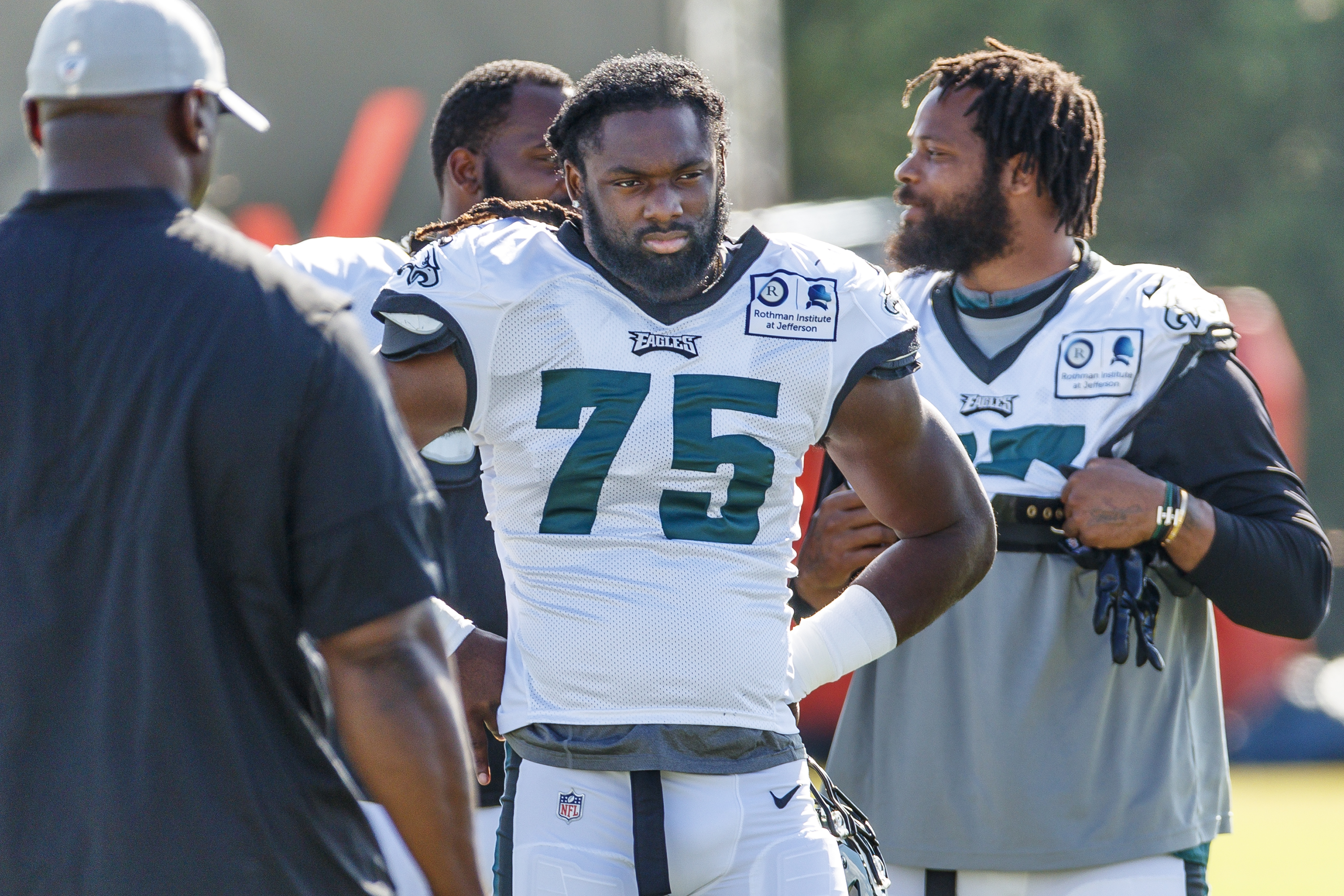 Josh Sweat (center) listens to his coach as Michael Bennett (right) and Fletcher Cox chat before practice on Thursday.