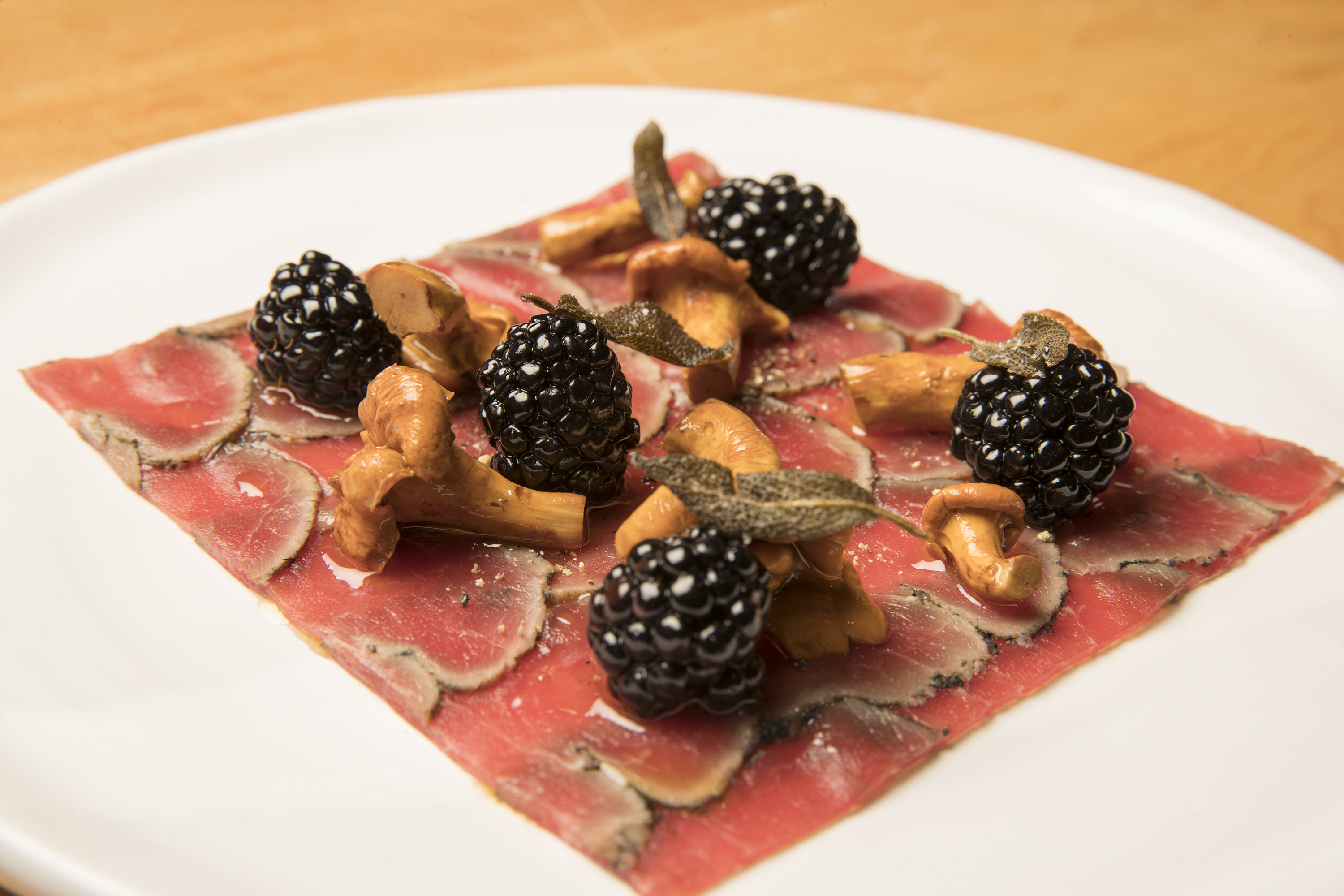 Veal carpaccio served with blackberries and chanterelles under oil at Andiario in West Chester.