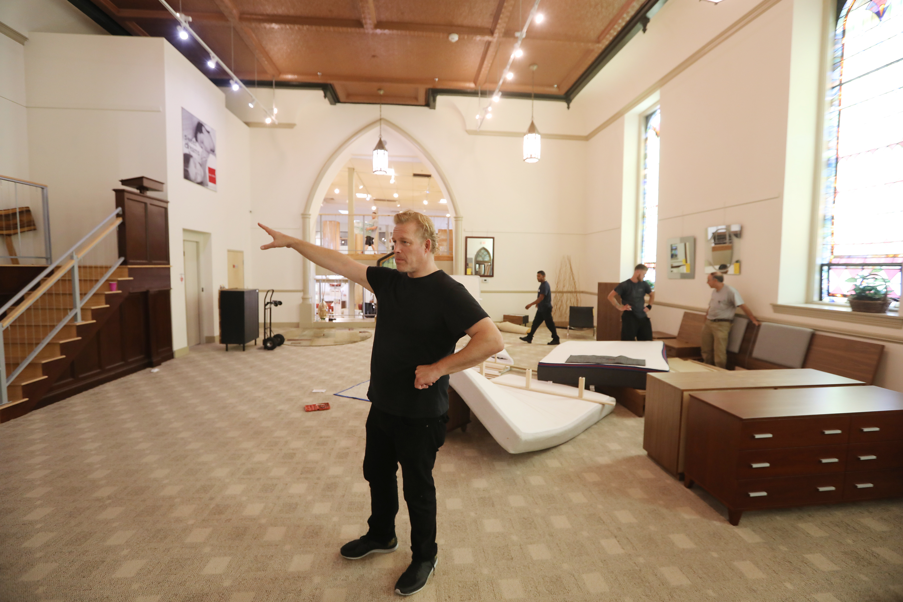 Dane Decor co-owner Drew Hamilton was orchestrating crews as they emptied portions of his Downingtown, Pa., store of furniture on Friday, Aug. 3, 2018. This part of the store, occupying the sanctuary of an 18th-century church, will be the dance floor for a wedding reception for the young mayor of his town. x