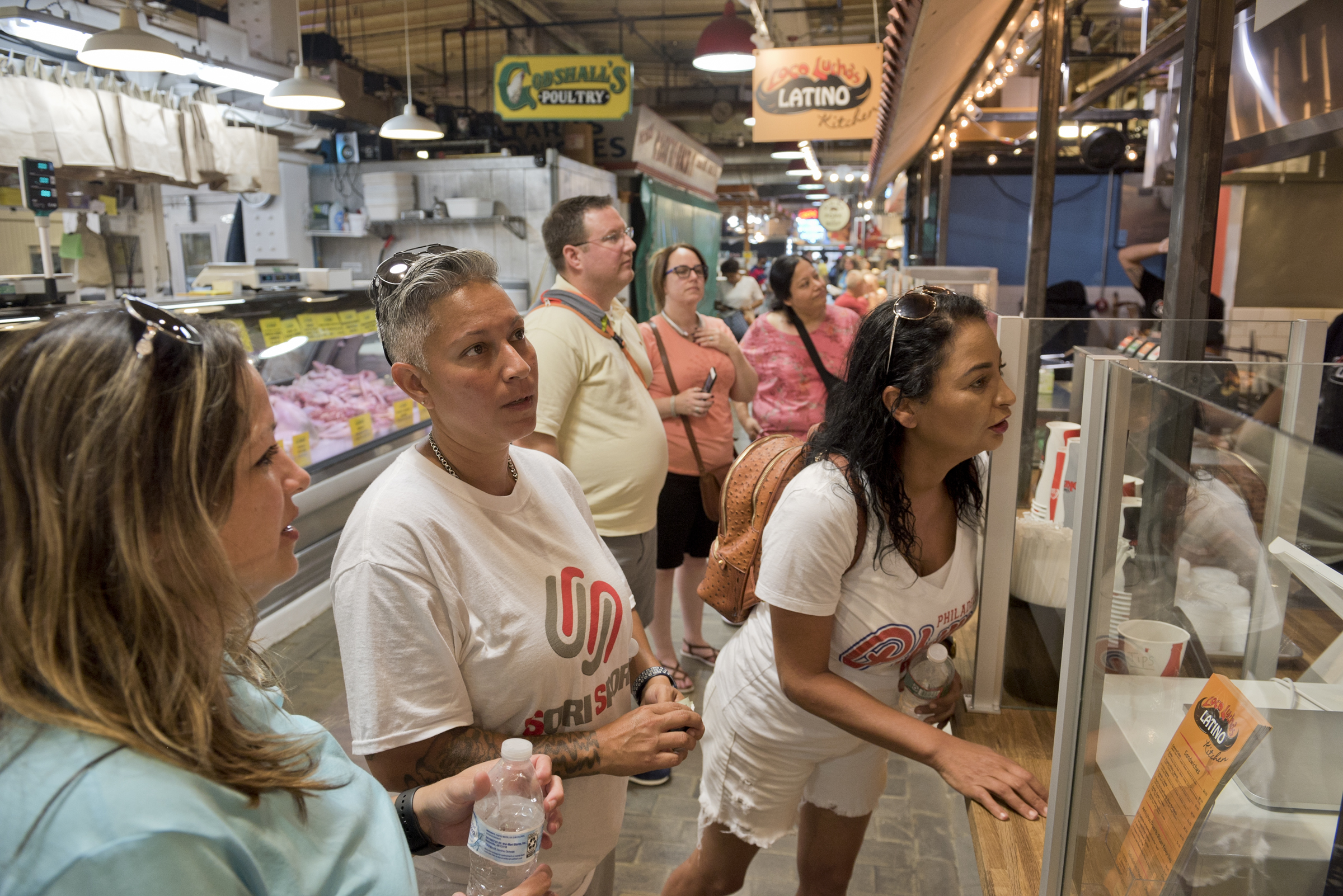 "From left to right, Soraida Perez, Daisy Lopez, and Carmen ""Milly"" Chevere Ortiz order lunch at a Puerto Rican food stand in the Reading Terminal Market on Monday, August 6."