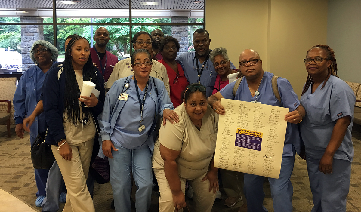 Workers at Chestnut Hill Hospital with the petition they delivered to management on Monday, July, 30, 2018.