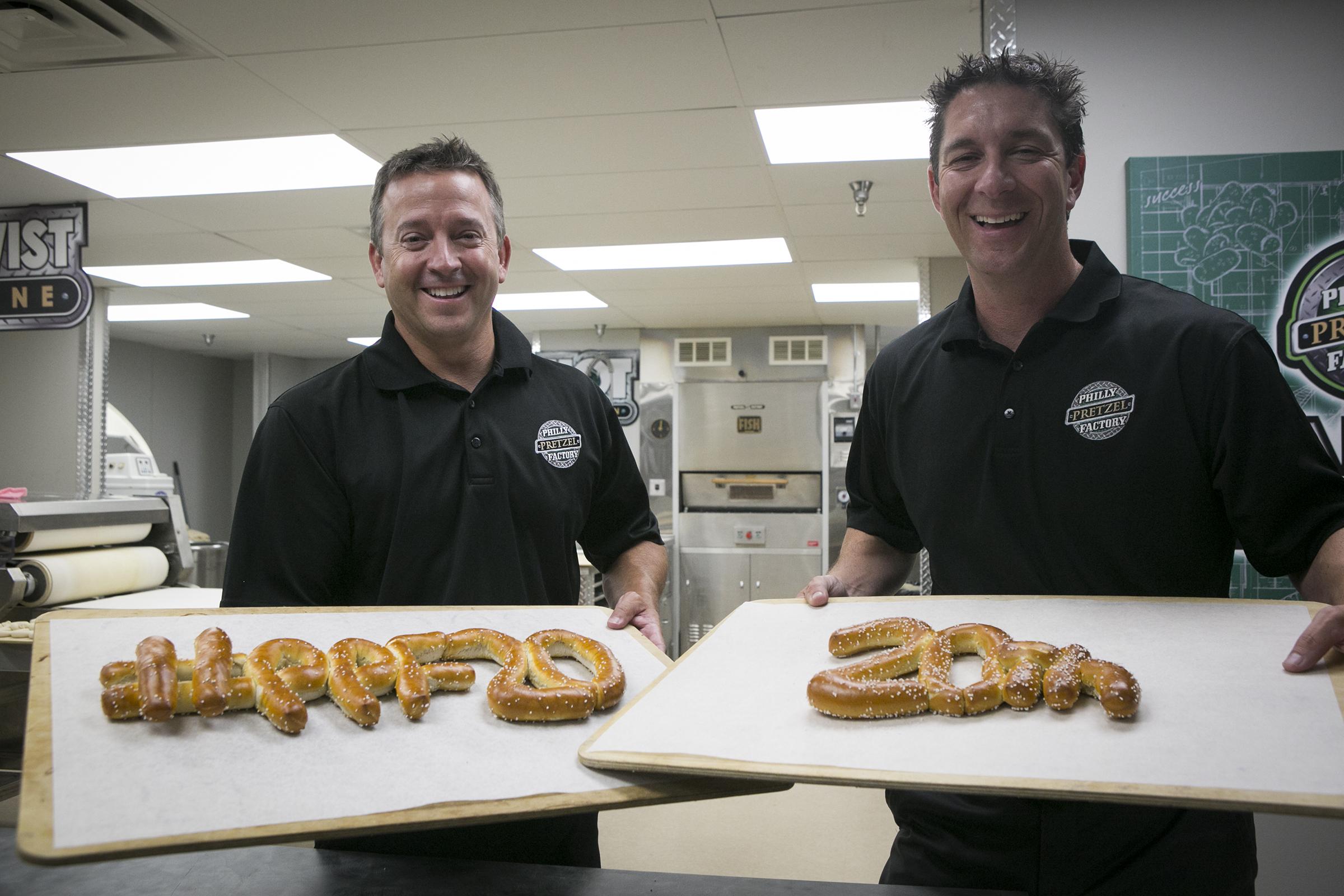 Philly Pretzel Factory co-founders Len Lehman (left) and Dan DiZio with celebratory pretzels in the test kitchen at Philly Pretzel Factory headquarters in Bensalem, Pa.