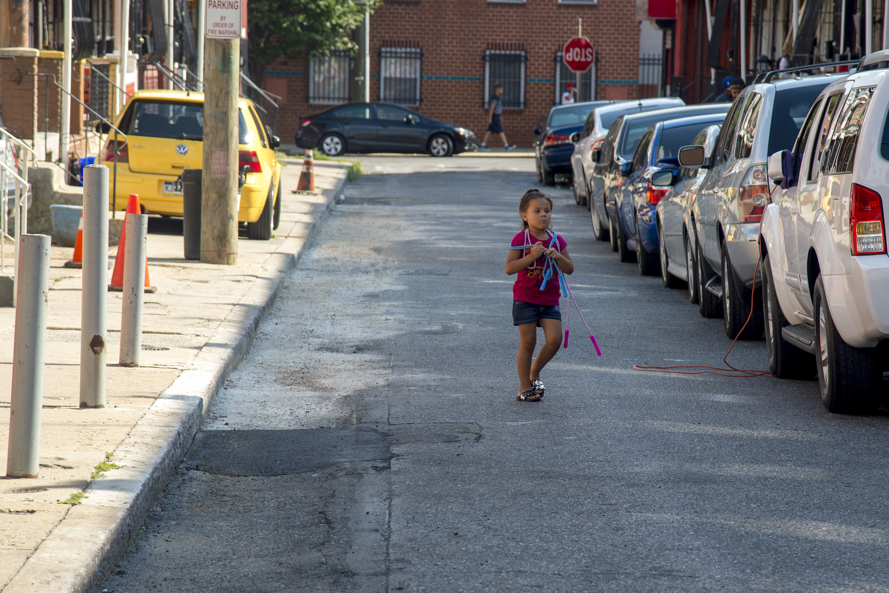 Maya Torres, 5. crosses her street on the 3300 block of Mutter Street August 9, 2018., where residents filled their own potholes (rear, lighter parts) after calling the city about it for three years. The streets department did finally come, and finished the job (front, black parts)