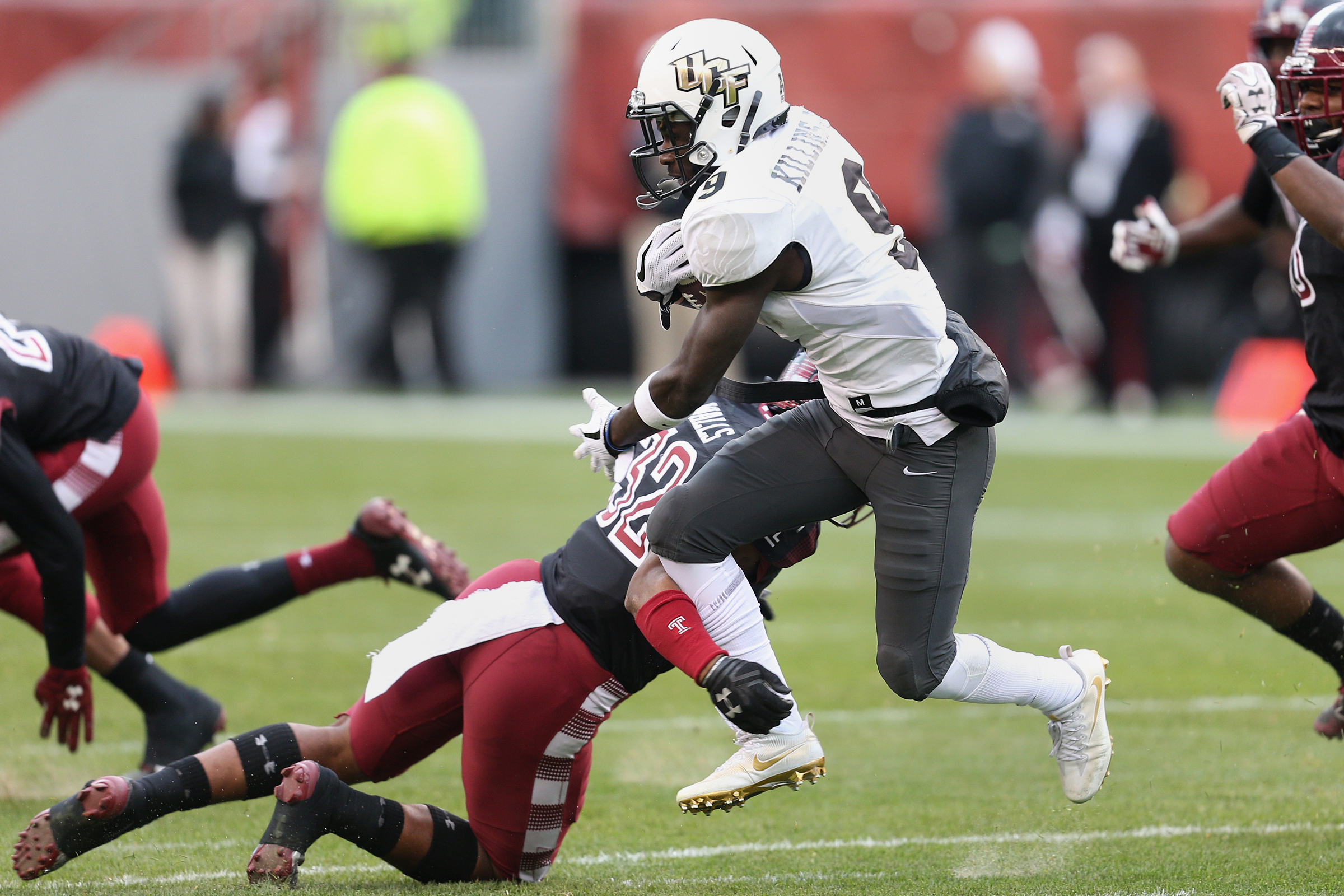 Temple defensive back Benny Walls (32) attempts to tackle UCF running back Adrian Killins Jr. (9) during a game at Lincoln Financial Field on Saturday, Nov 18, 2017. TIM TAI / Staff Photographer
