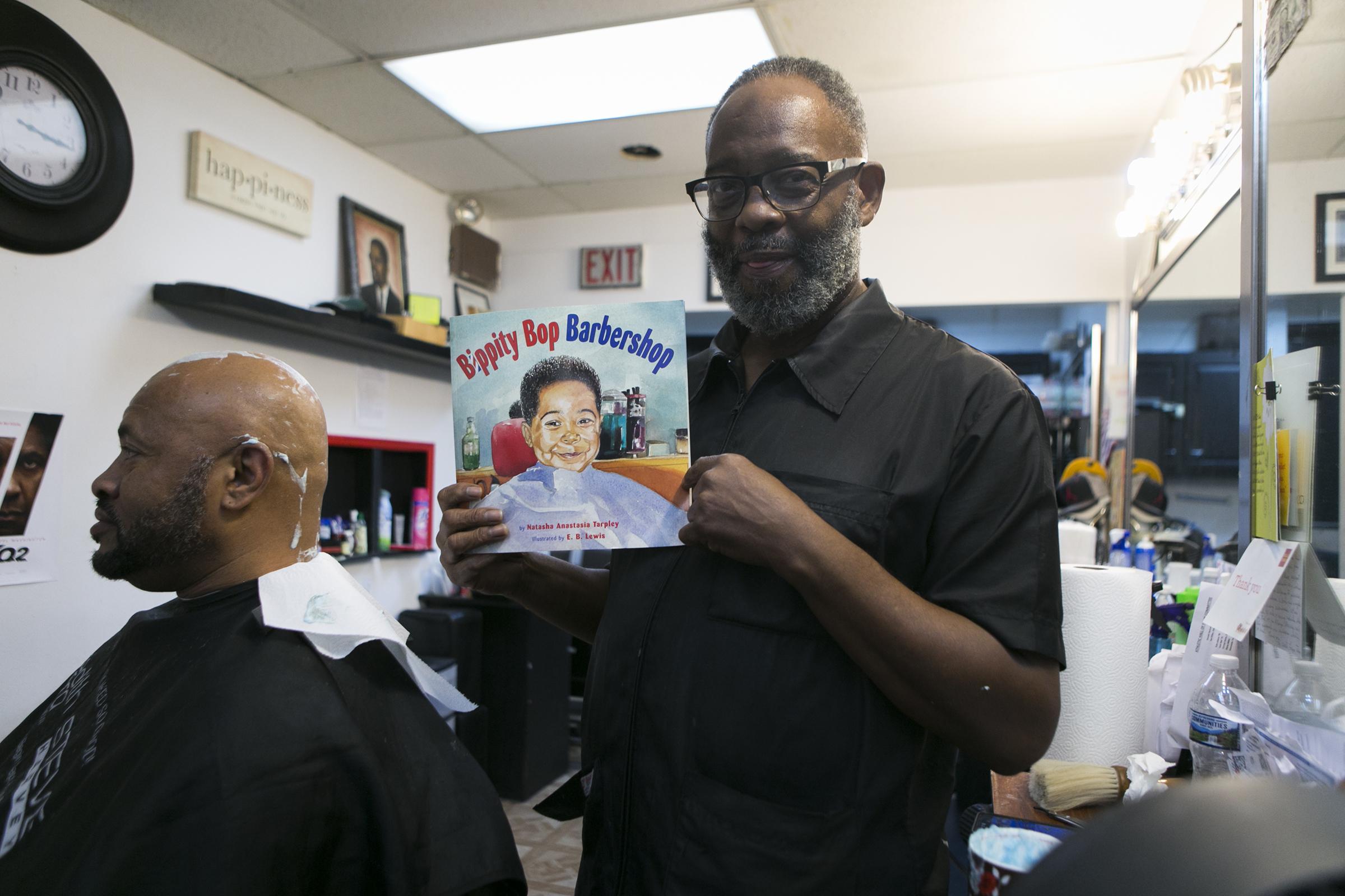 Leroy Robinson Jr., owner of Leroy´s Barbershop on Lancaster Avenue, poses with one of his favorite books, Bibbity Bop Barbershop.