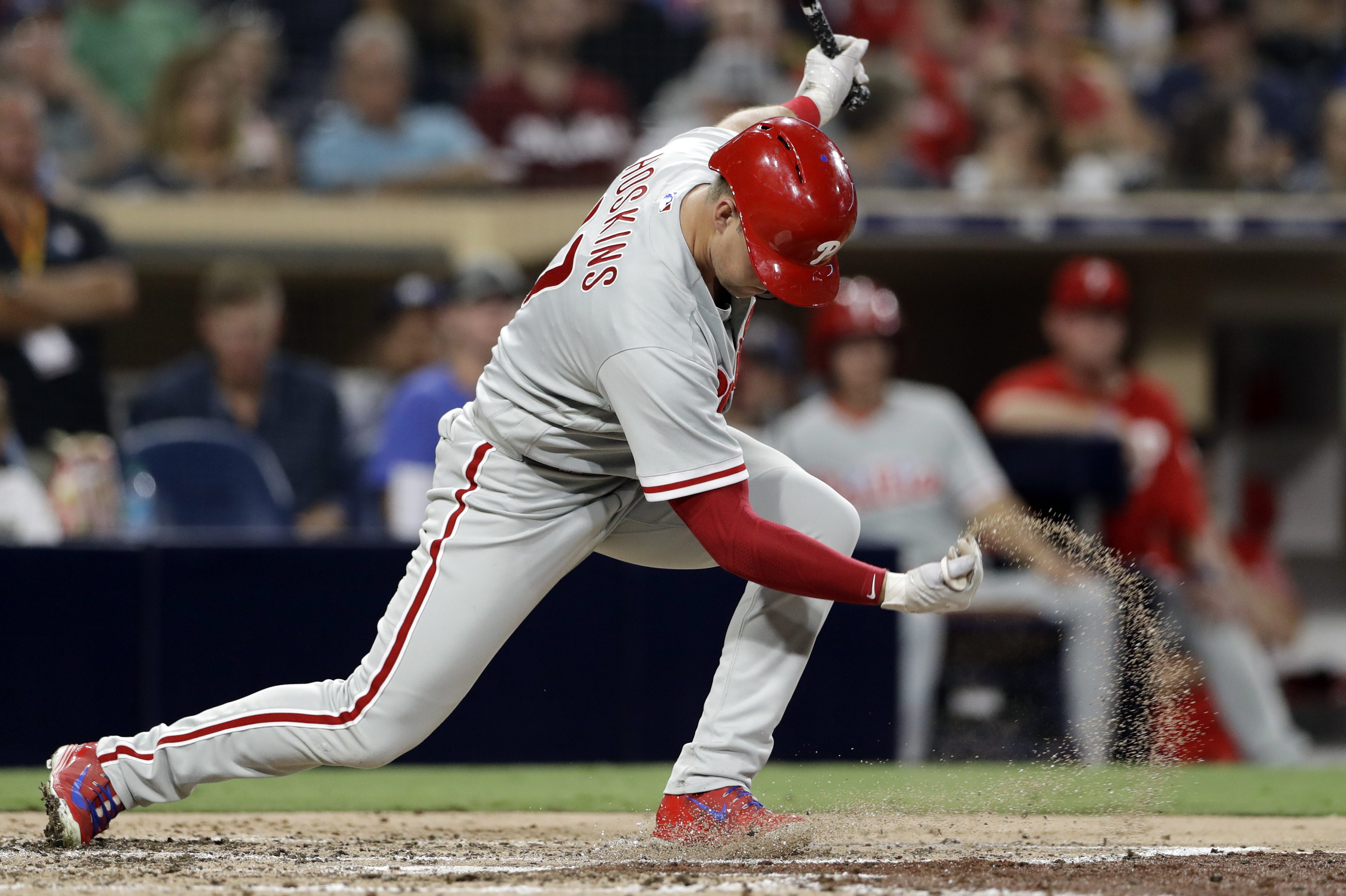 Rhys Hoskins throws a handful of dirt after striking out during Friday´s loss to the Padres.