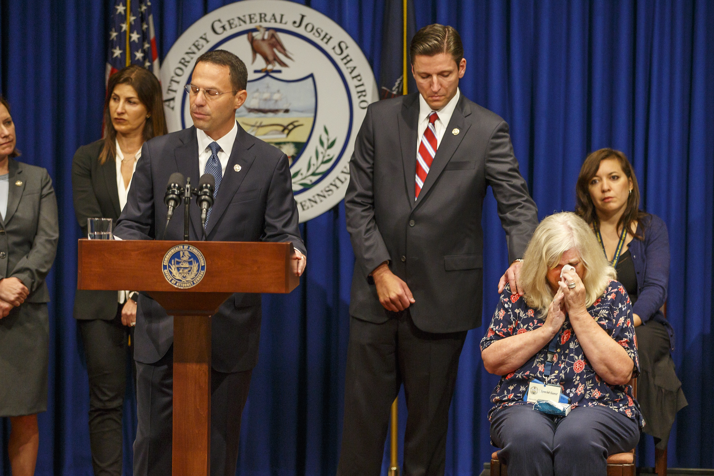 Daniel J. Dye, center, Senior Deputy Attorney General, center, reaches over and comforts Judy Deavena, right, mother of Joey Behe, a victim of sexual abuse from a Catholic priest, as Pennsylvania attorney general Josh Shapiro unveils a grand jury report into abuse at six dioceses across the state.