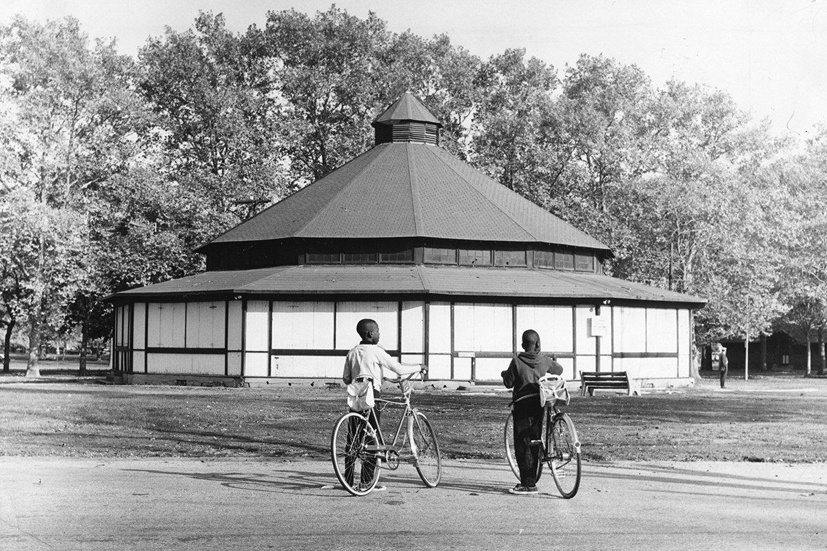 Two boys with their bicycles, stand outside of a merry-go-round pavilion in Hunting Park.