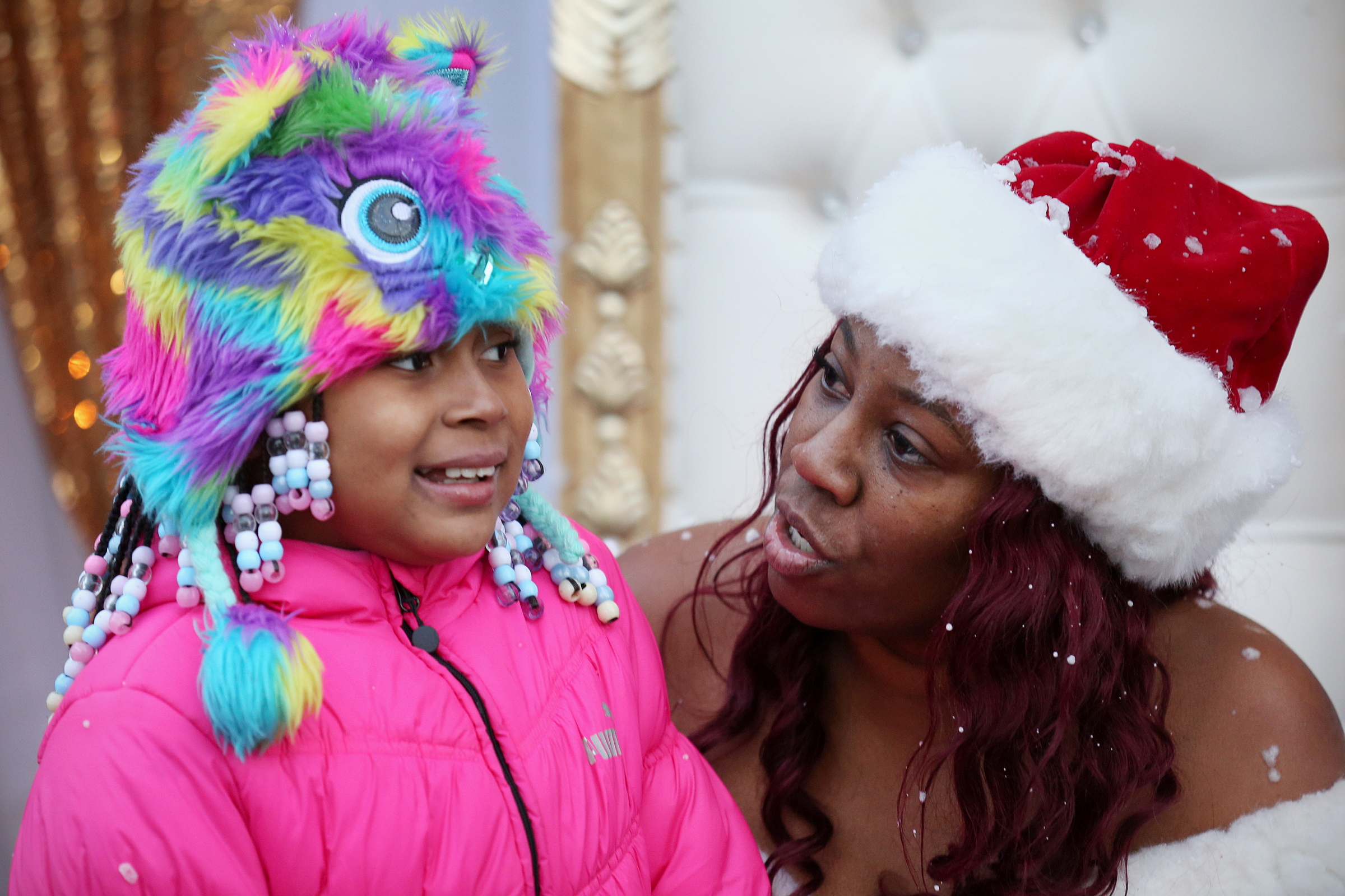 Saudia Shuler, dressed as �Saudi Claus,� talks to Destani Patterson, 8, during a Christmas toy giveaway in front of Shuler�s restaurant, Country Cookin, in North Philadelphia back in December, 2017.