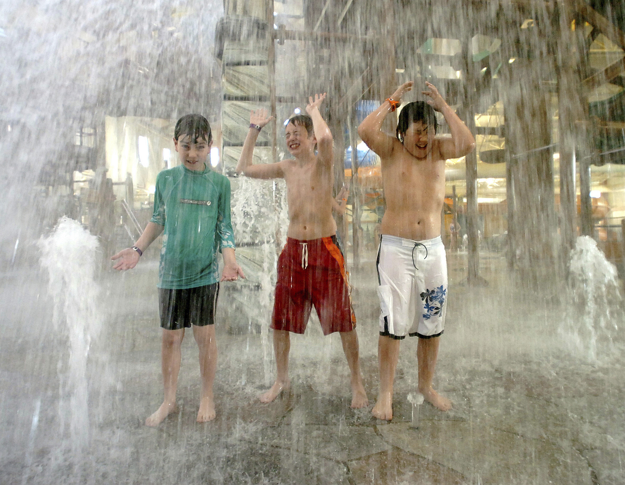 In this Oct. 26, 2005, file photo, Collin Bevan (left), Keith Casares (center), and Jared Kubalak, right, all from Cresco, Pa., play under a rush of water at Great Wolf Lodge in Scotrun, Pa.