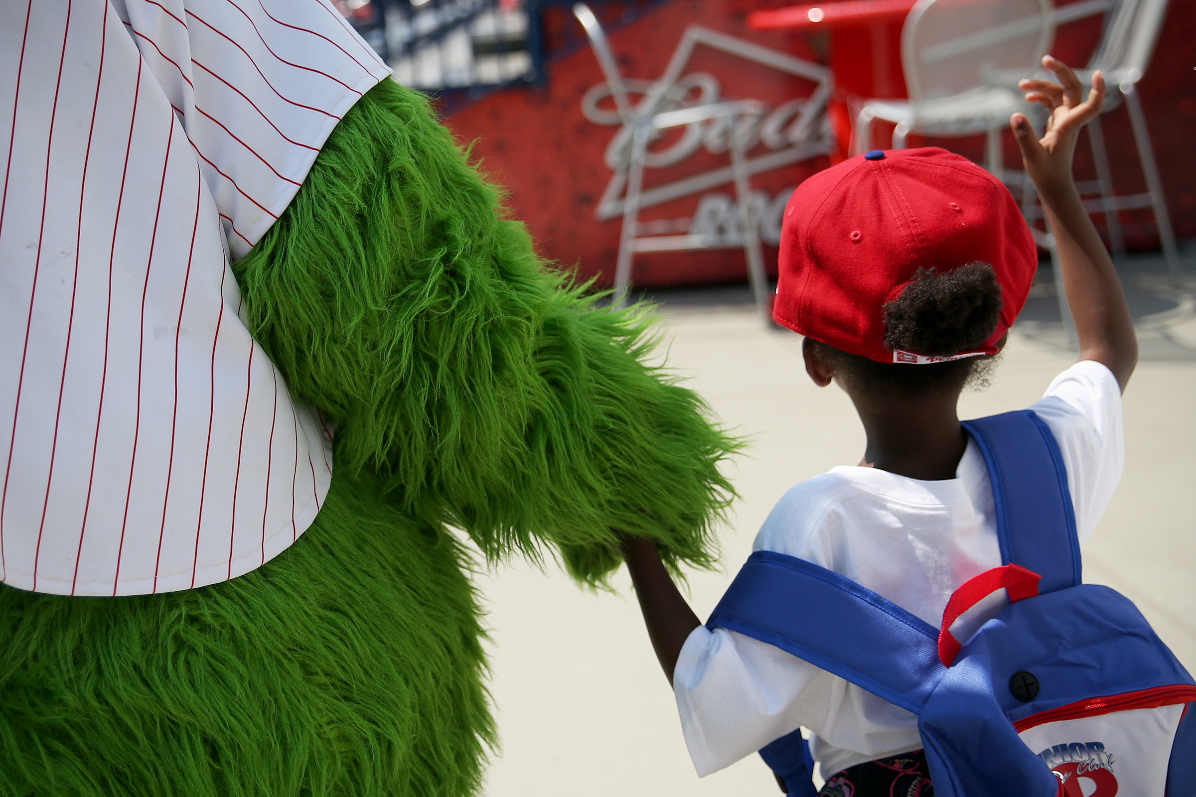 The Phillie Phanatic holds the hand of Zariah Brown, 5, who is about to begin kindergarten at Gilbert Spruance Elementary School, at a news conference to promote Philadelphia´s first day of school, Aug. 27.