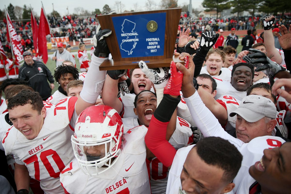 Delsea players celebrate with South Jersey Group 3 championship trophy after 29-28 victory over Woodrow Wilson last December at Rowan University.