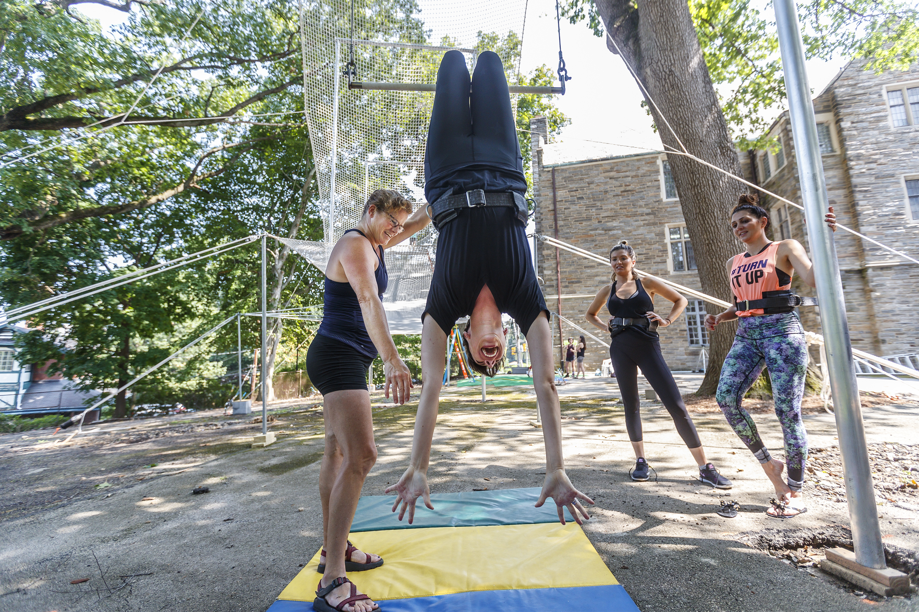 With flying trapeze program director, Mary Kelly Rayel, left, to help her, a first time trapeze student learns the correct way to hang upside down on the bar and hold her hands, at the Philadelphia School of Circus Arts on Wednesday Agust 15, 2018.