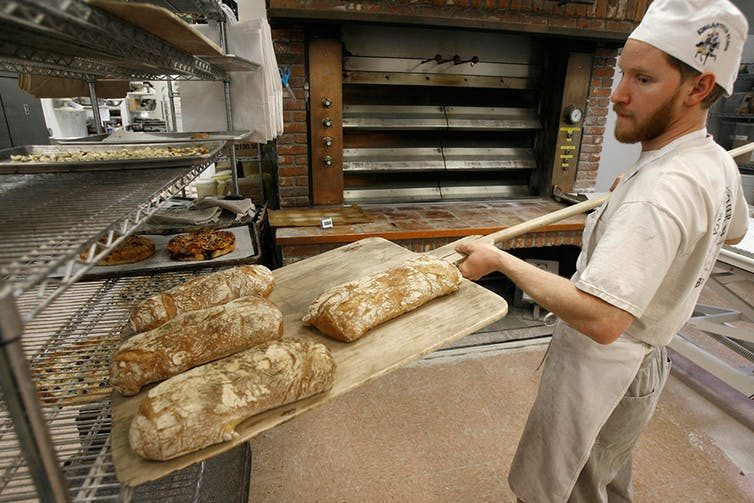 An employee at employee-owned King Arthur Flour Co. in Norwich, Vermont, takes bread from the oven.