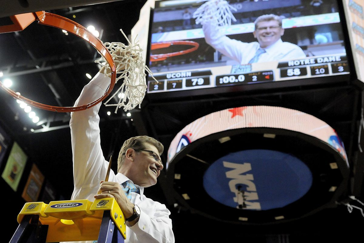 Connecticut head coach Geno Auriemma raises the net after his team won the national championship in 2014.