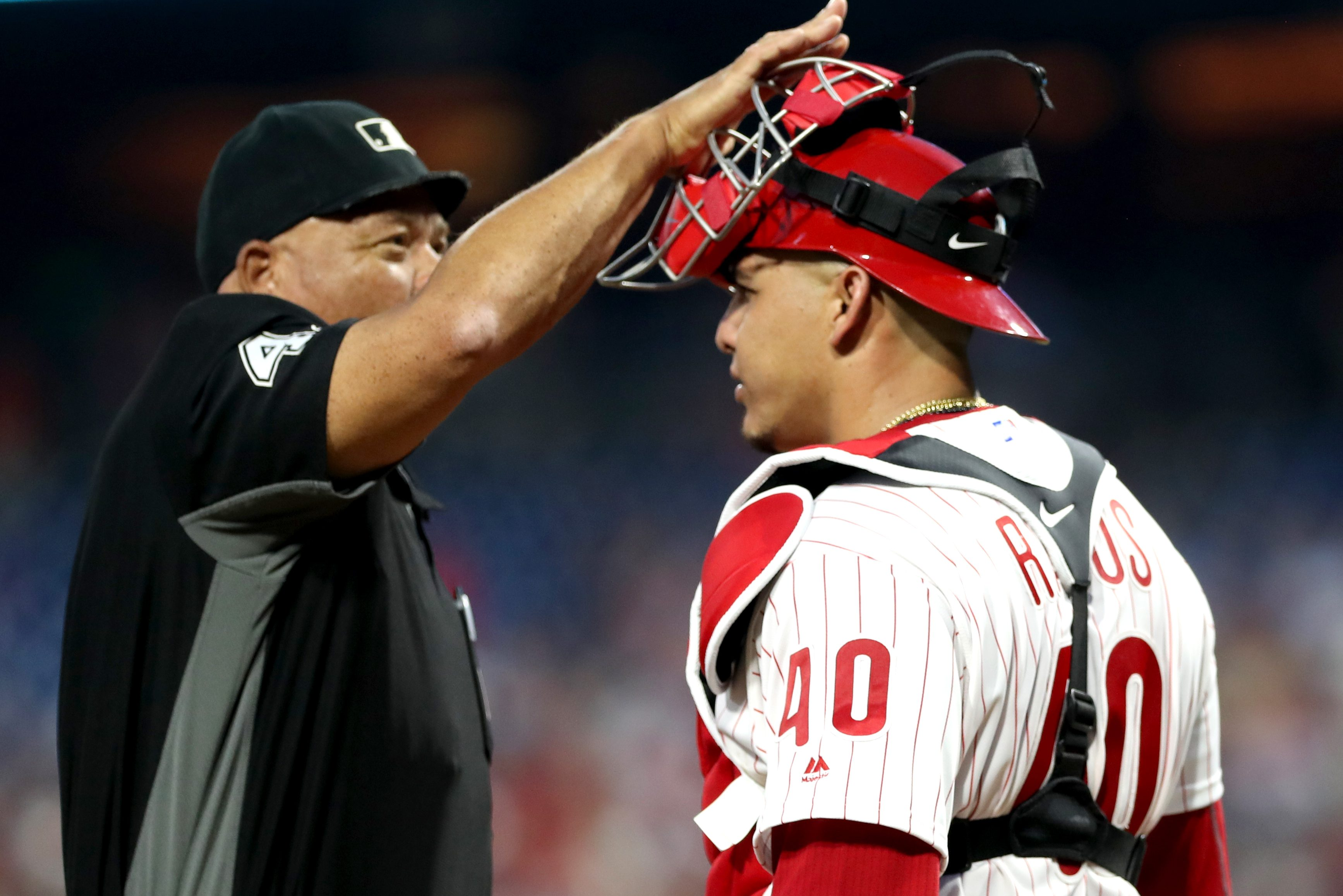 Home plate umpire Kerwin Danley, left, slaps Wilson Ramos of the Phillies on his catcher´s mask, showing where the umpire was hit during the Phillies´ 7-4 win over the Red Sox on Wednesday.