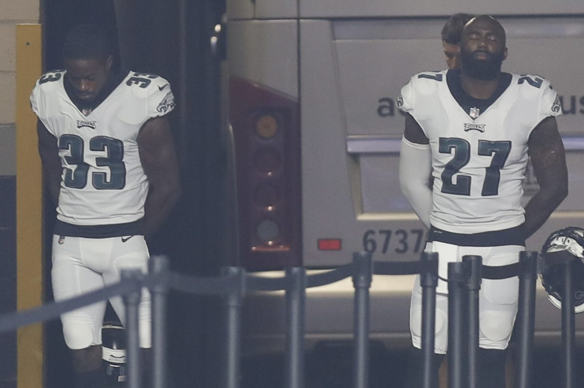 Eagles defensive backs Malcolm Jenkins and De'Vante Bausby stands in the Eagles tunnel during the national anthem before their preseason game against the Patriots on Thursday.