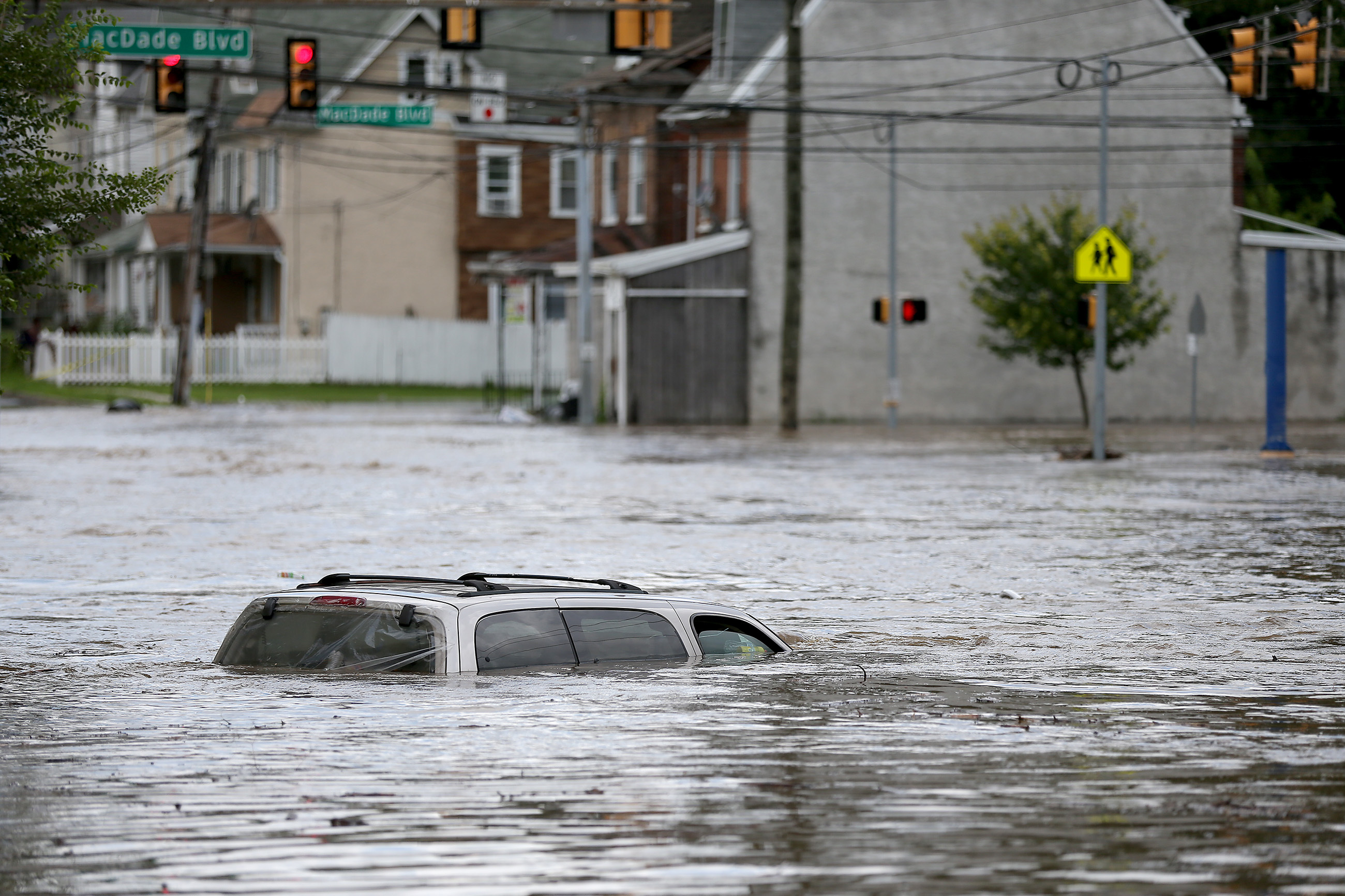 A vehicle sits in flood waters from Darby Creek on Springfield Road in Darby, PA on August 13, 2018.