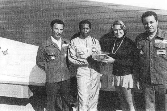"""Tommy Thompson, second from left, receives an award from the Sports Car Club of America in 1977. To his left is crewman Kenny Wright, and his right an unidentified """"trophy queen"""" and his manager, Tim."""