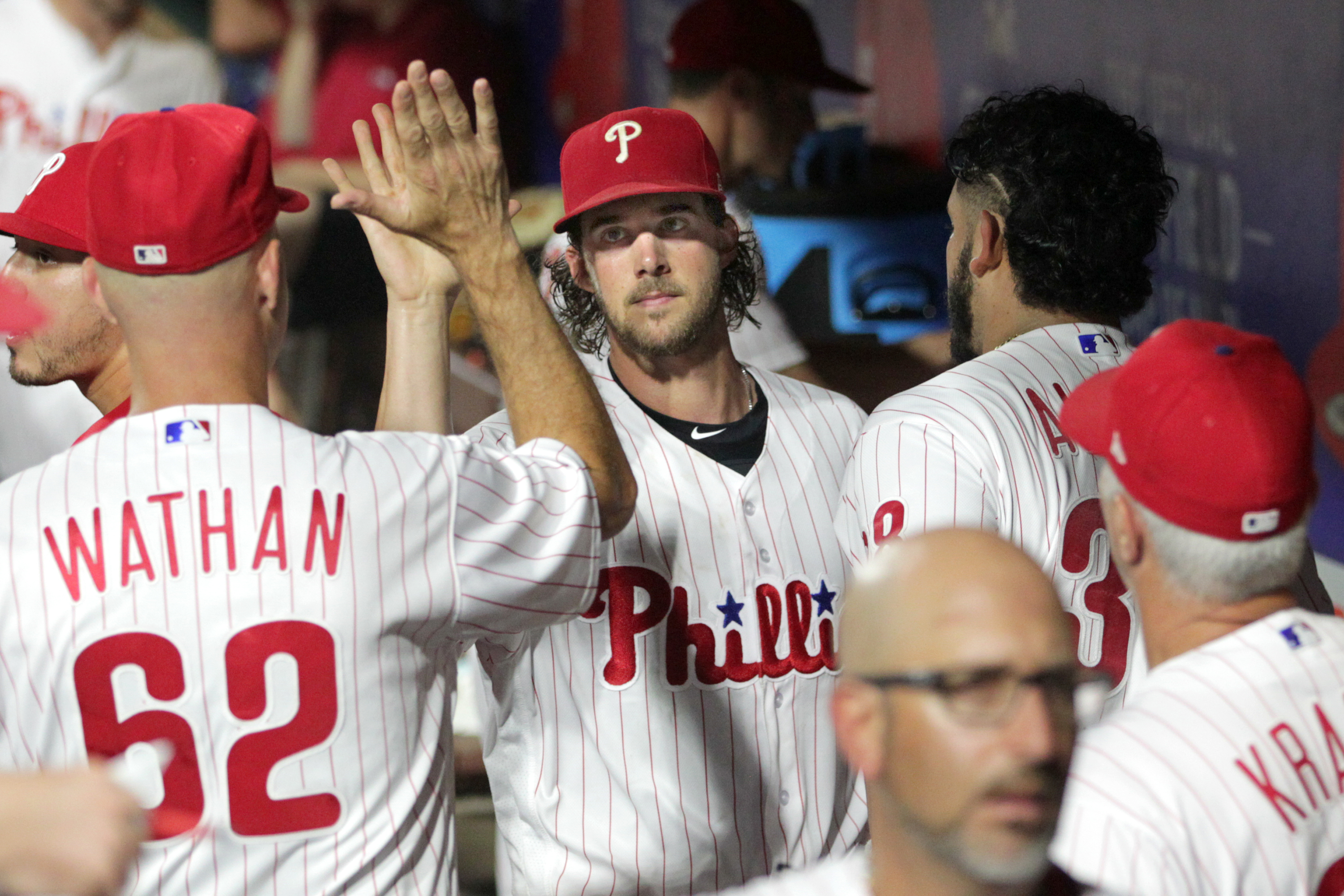 Aaron Nola, center, of the Phillies is congratulated by teammates and coaches including coach Dusty Wathan, left, after pitching his final inning agaist the Mets at Citizens Bank Park on August 17, 2018.